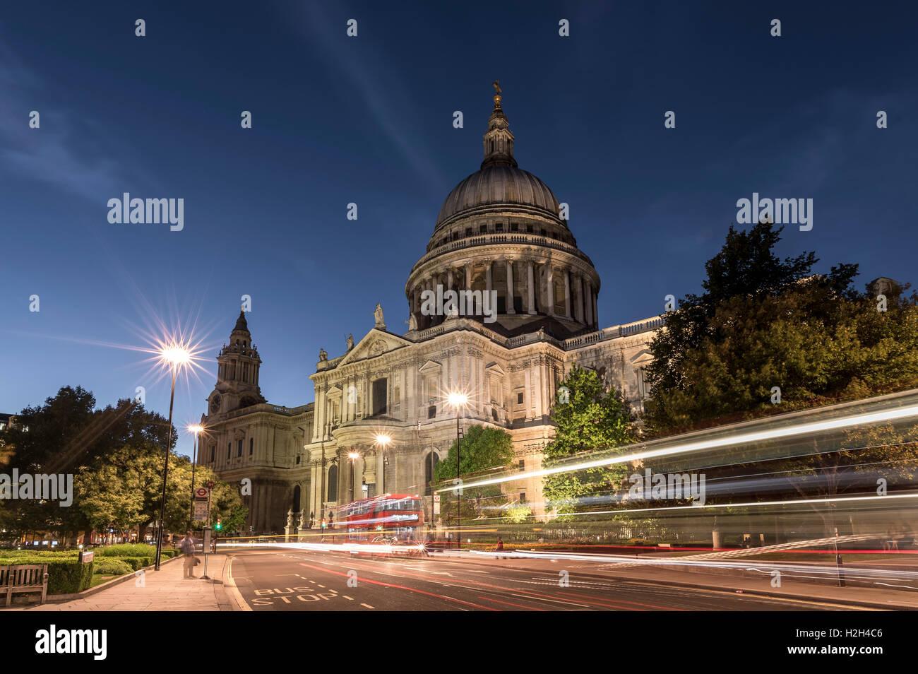 St. Pauls Cathedral, nachts, mit Verkehr wegen der Londoner Busse auf der Straße im Vordergrund des Bildes Stockbild
