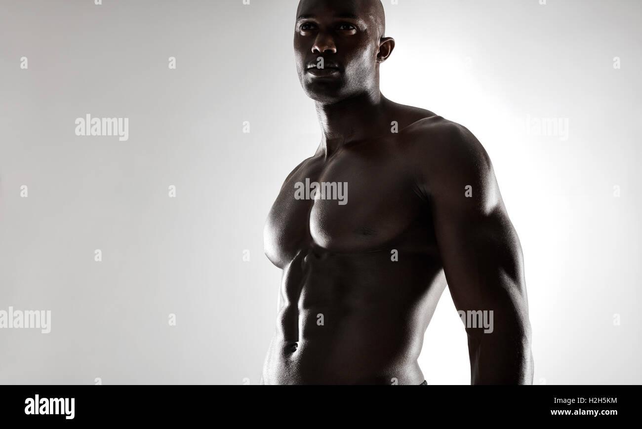 Studioaufnahme von muskulöser Mann posiert vor grauem Hintergrund ...