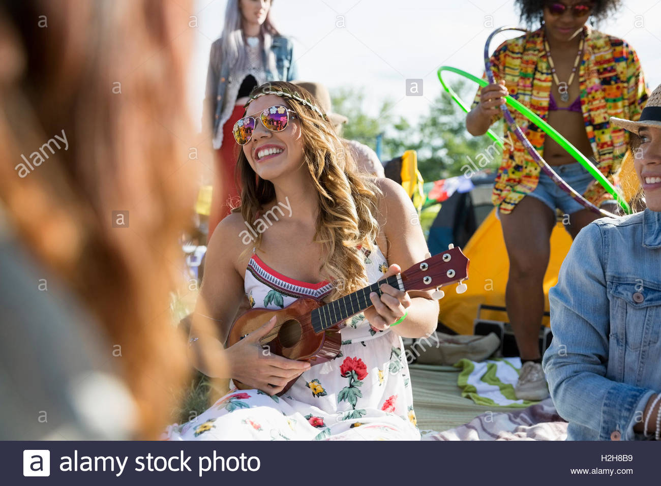 Junge Frau spielt Ukulele auf Sommer Musik Festival-Campingplatz Stockbild