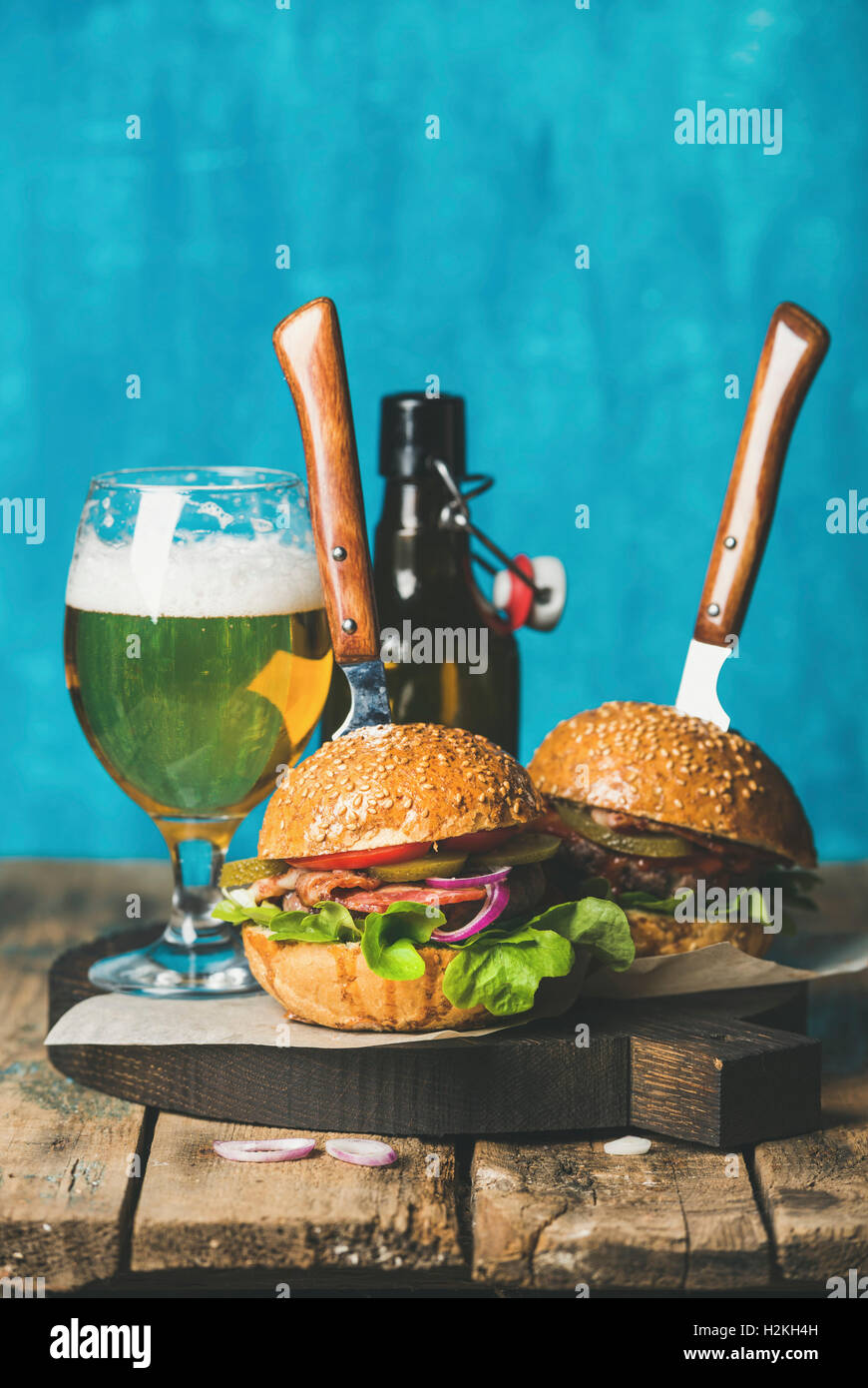 Zwei hausgemachte Rindfleisch-Burger mit knusprigem Speck, Zwiebeln, Gurken, Gemüse, Glas und Flasche Weißbier Stockbild