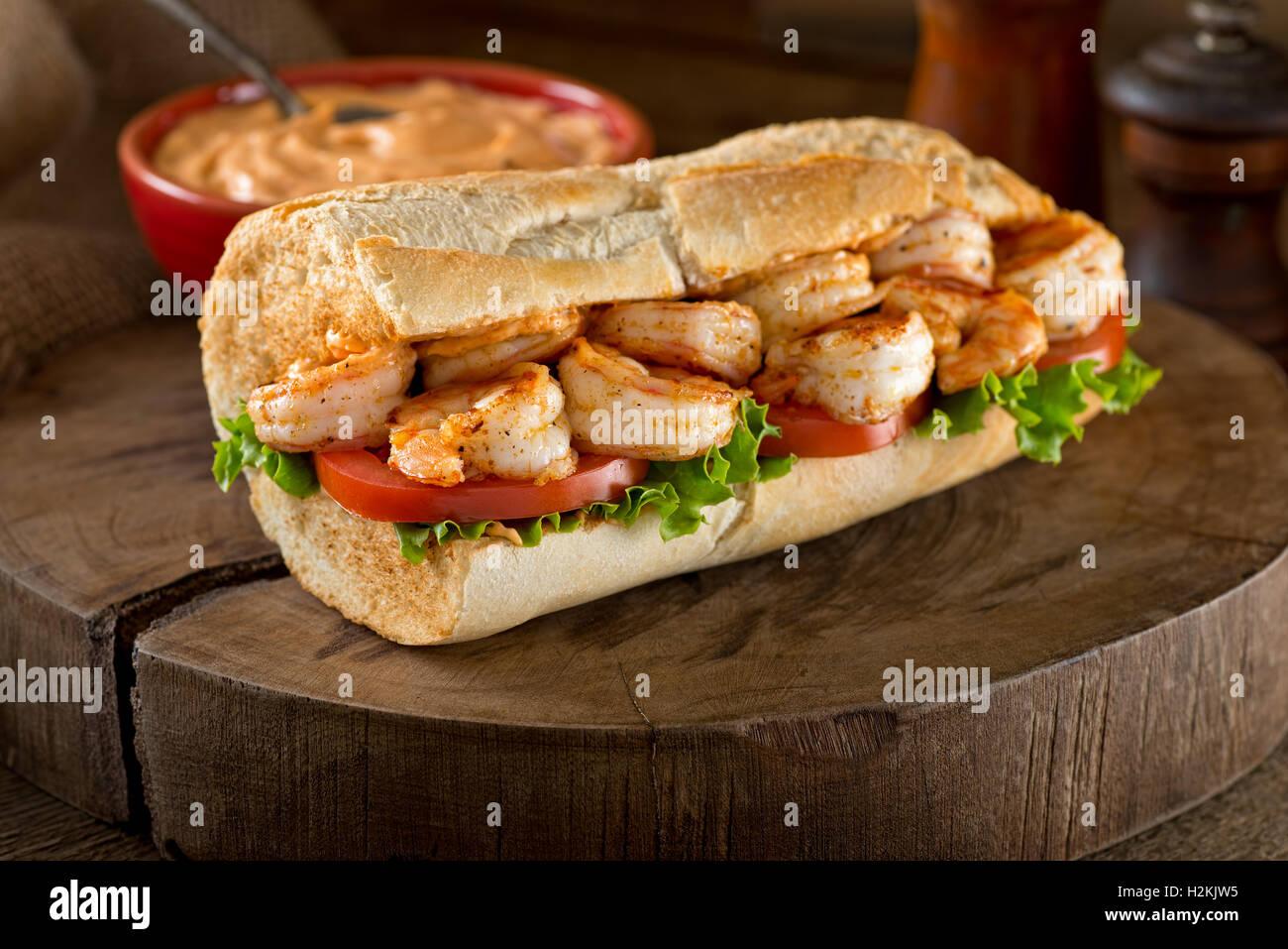 Ein lecker hausgemachten gegrillte Garnelen Po Boy Sandwich auf Baguette mit Salat, Tomate und Remoulade gekleidet. Stockbild