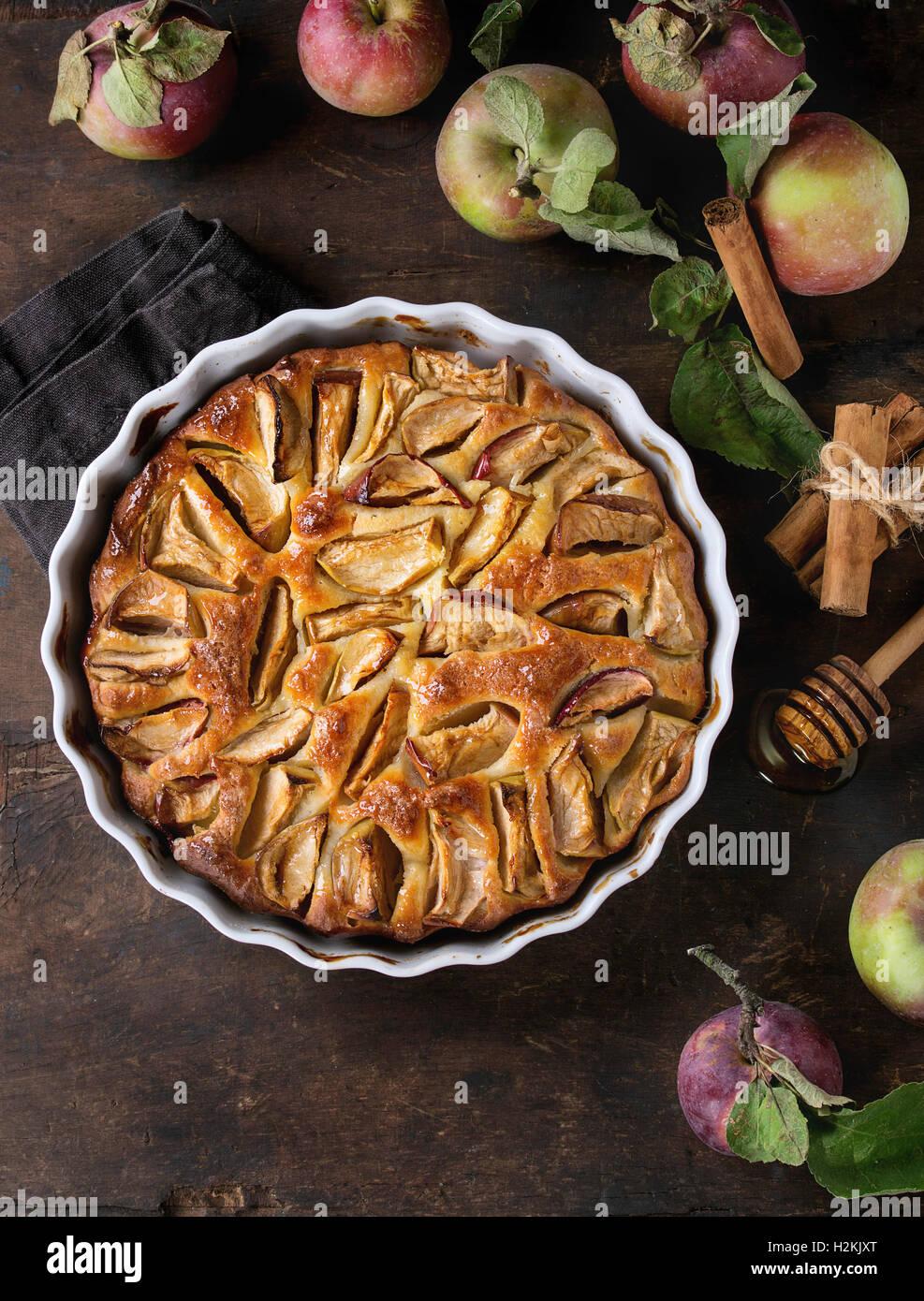 Hausgemachte Kuchen Apfelkuchen in weißer Keramik Form mit frischen Äpfeln mit Blättern, Honig und Stockbild