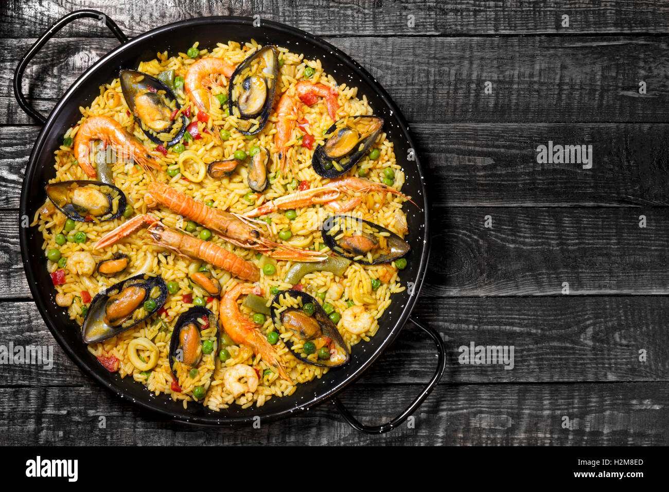 Spanische Paella auf einem dunklen Holztisch mit textfreiraum auf der rechten Seite Stockbild
