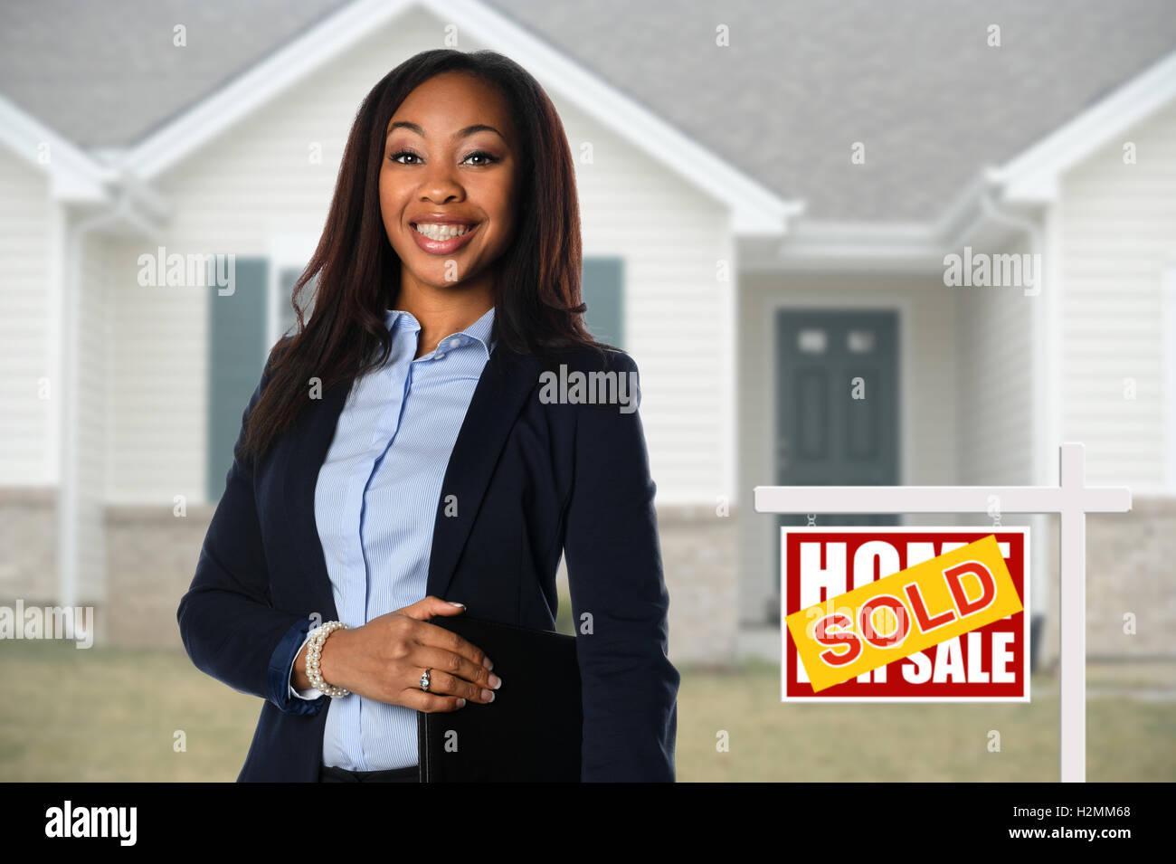 Schöne African American Real Estate Agent inf vor dem verkauften Haus Stockbild