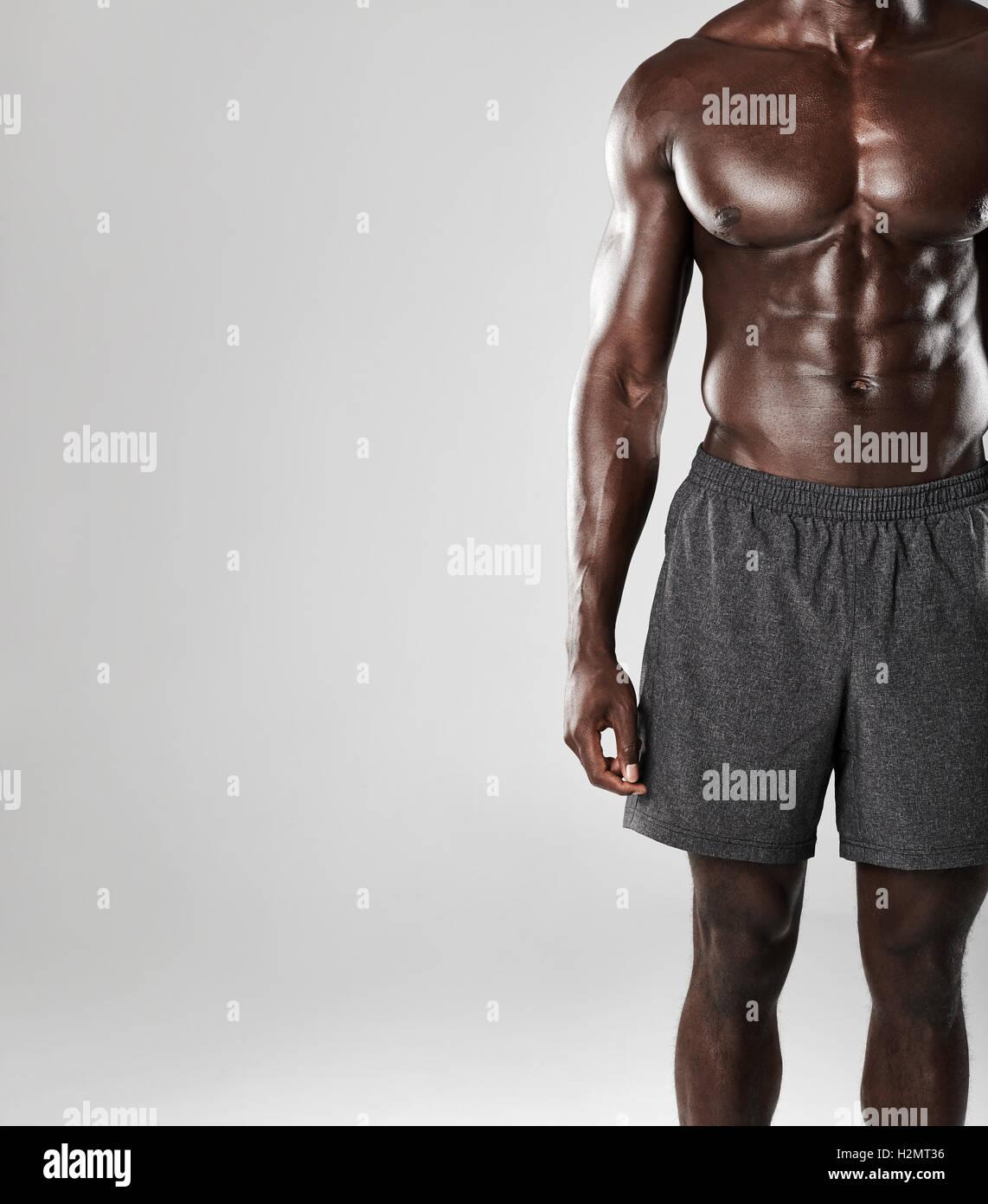 Schuss von jungen afrikanischen muskulöser Mann Körper vor grauem ...