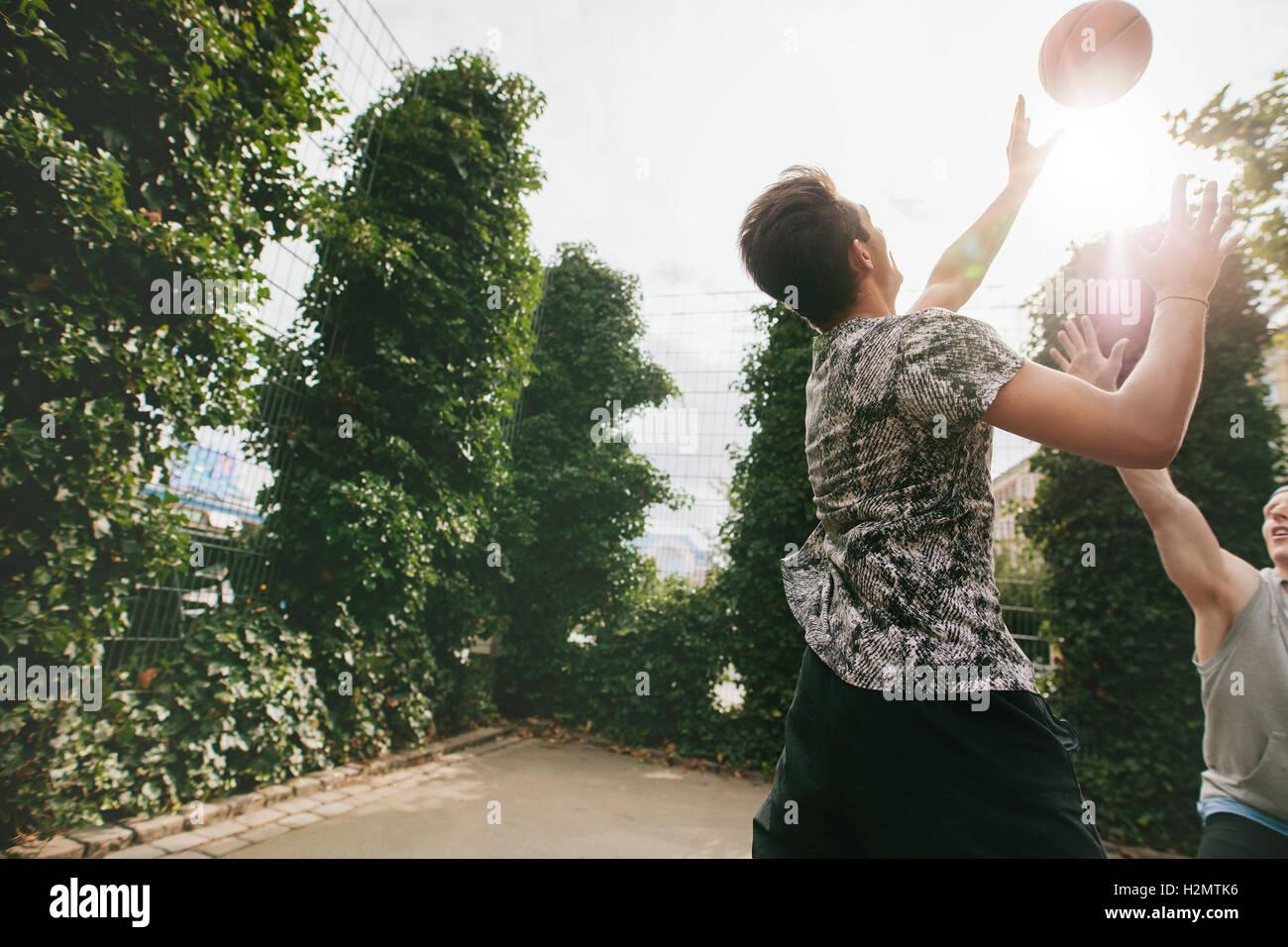 Freunde, Basketball gegeneinander spielen und Spaß am Außenpool. Zwei junge Männer Basketball zu Stockbild