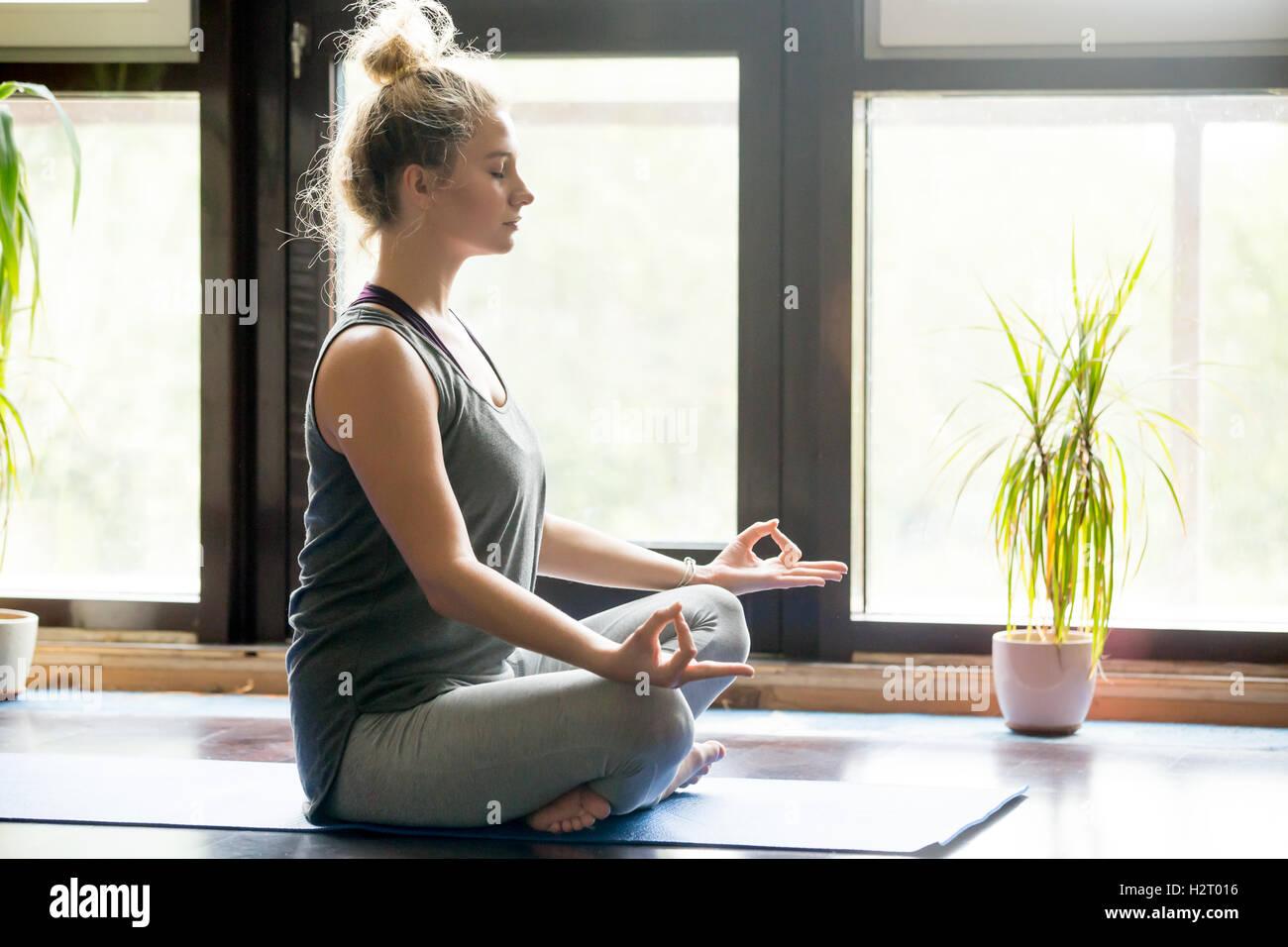 Yoga zu Hause: sinnende Frau Stockbild