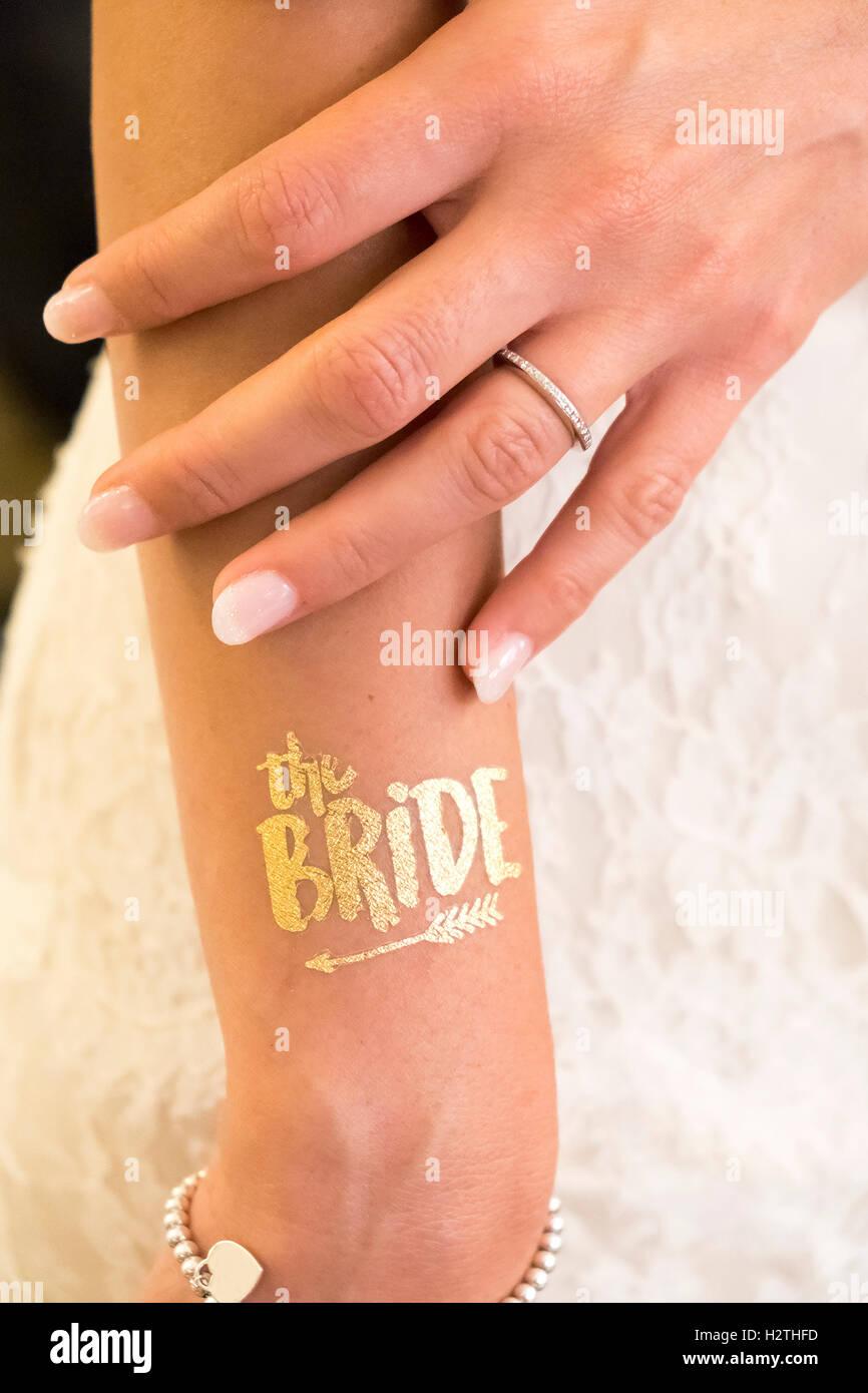 weibliche Hand zeigen Ehering und Text Braut goldenen Glitzer tattoo Stockbild