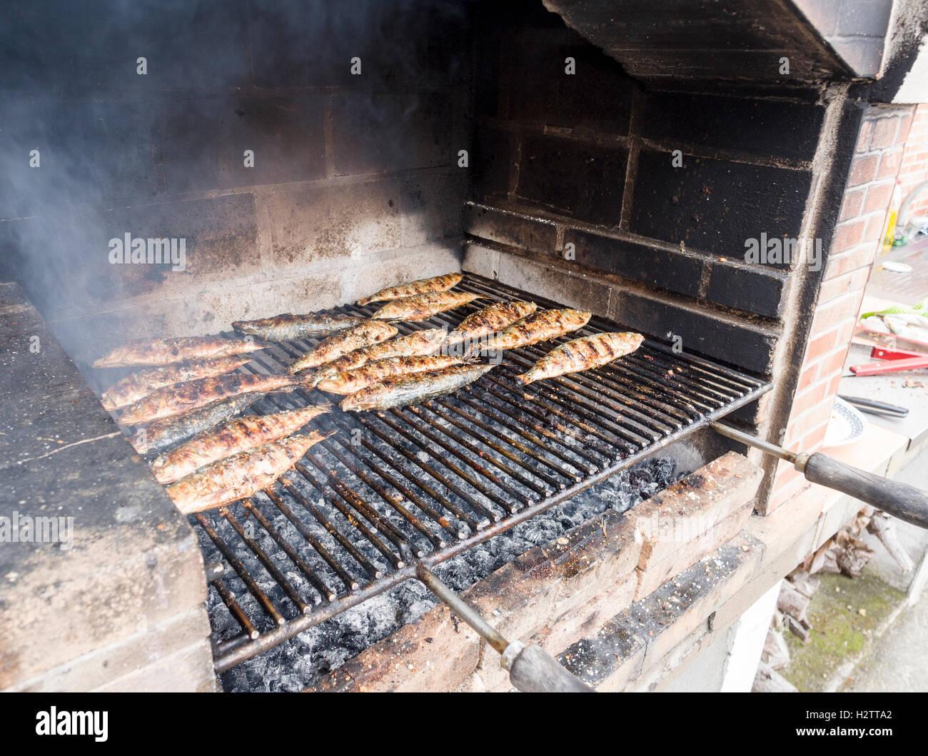 Sardinen auf einem Wirtschaftsinstrument Grill rösten. Ein Grill Grillen voller Sardinen oder Makrelen kocht Stockbild