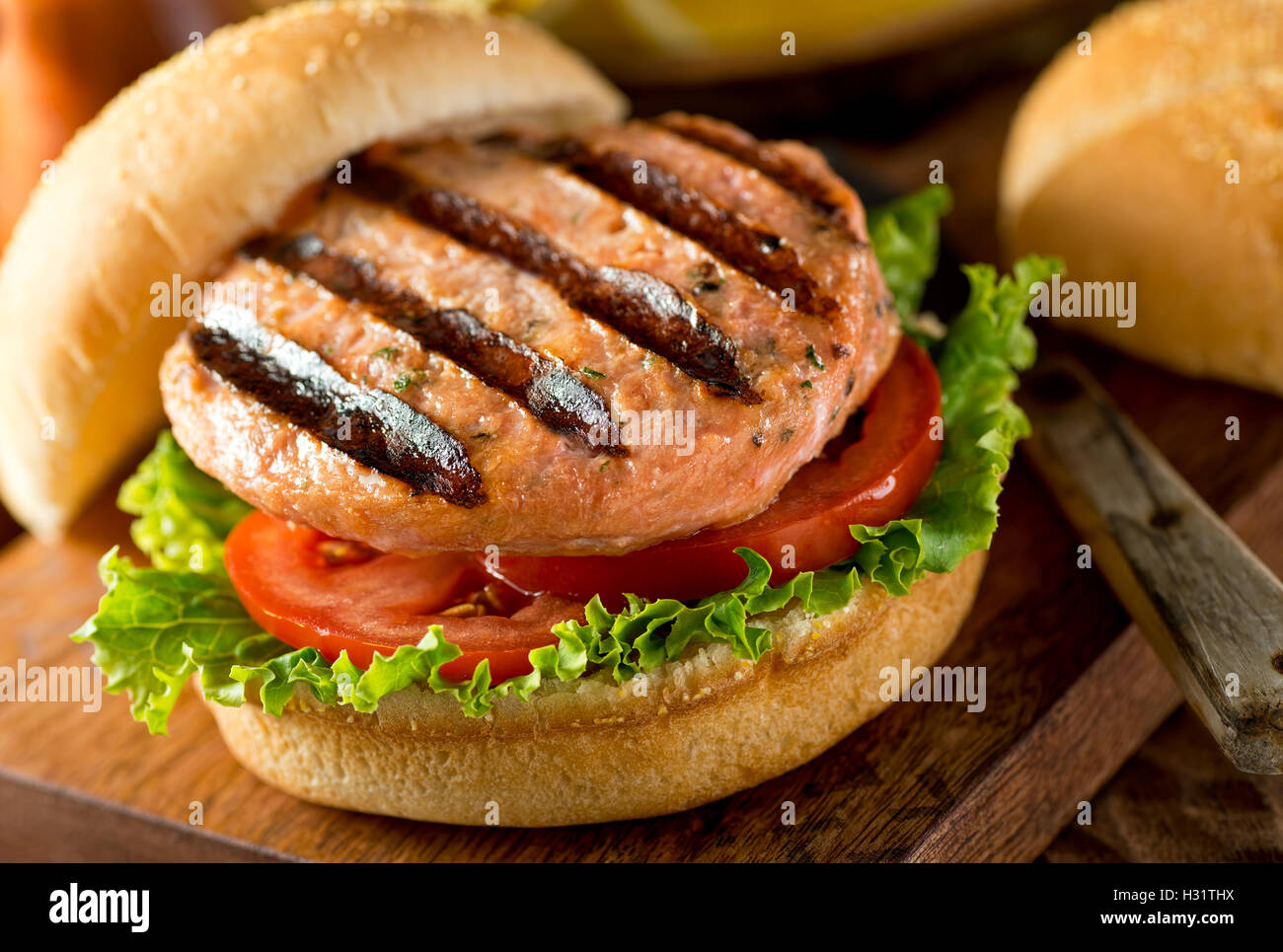 Eine köstliche hausgemachte gegrillten Lachs Burger mit Tomaten und Salat auf einem Brötchen. Stockbild