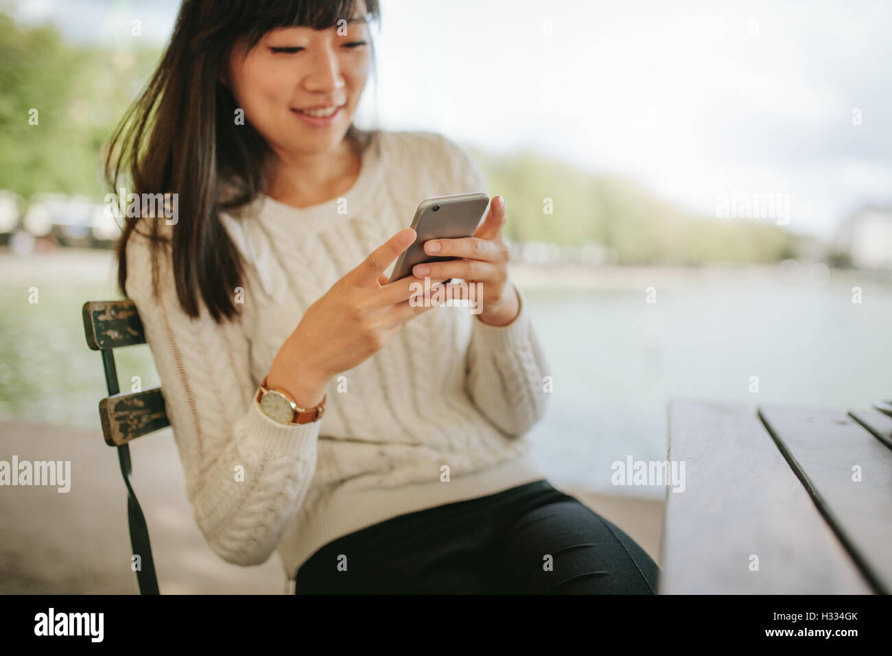 Schuss der glückliche junge Frau mit Handy in Straßencafé. Junge Frau am Tisch lesen SMS-Nachricht Stockbild