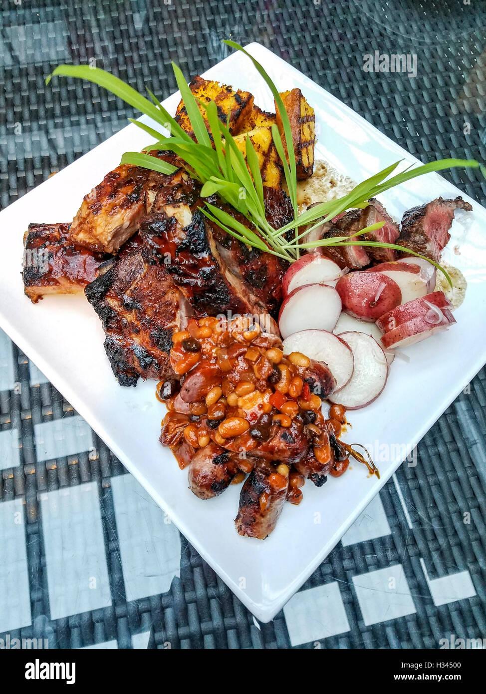 Verschiedene gegrillte Fleischsorten (Steak, Rippchen, Würstchen aus Schweinefleisch) diente während Farm Stockbild