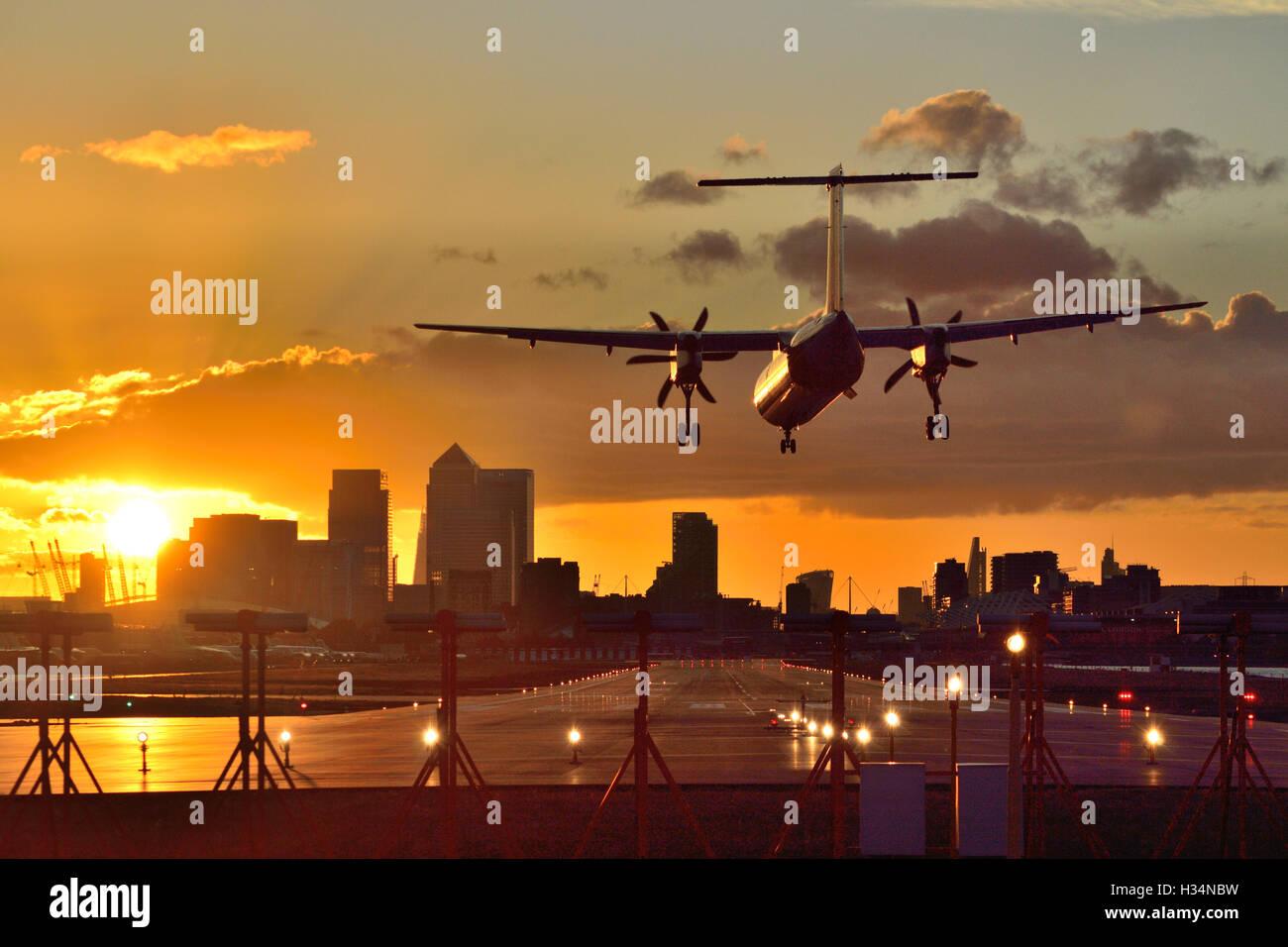 FlyBe Dash-8 kommt am London City Airport zu landen, wenn die Sonne untergeht. Stockfoto