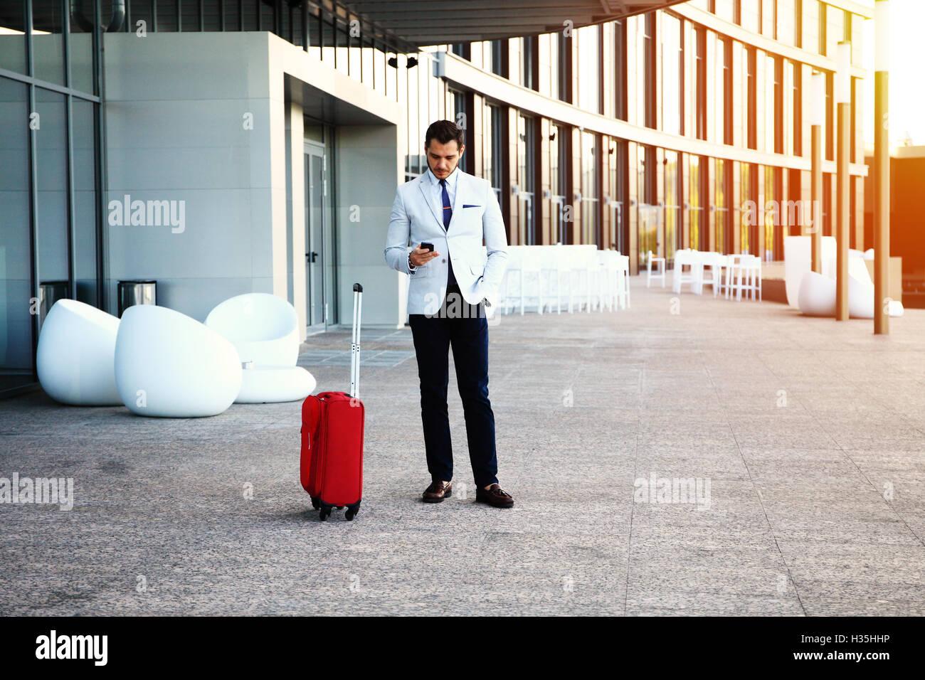 Jungen glücklich Reisenden Geschäftsmann Anruf nach der Ankunft im Hotel außerhalb mit seinem Gepäck. Stockbild
