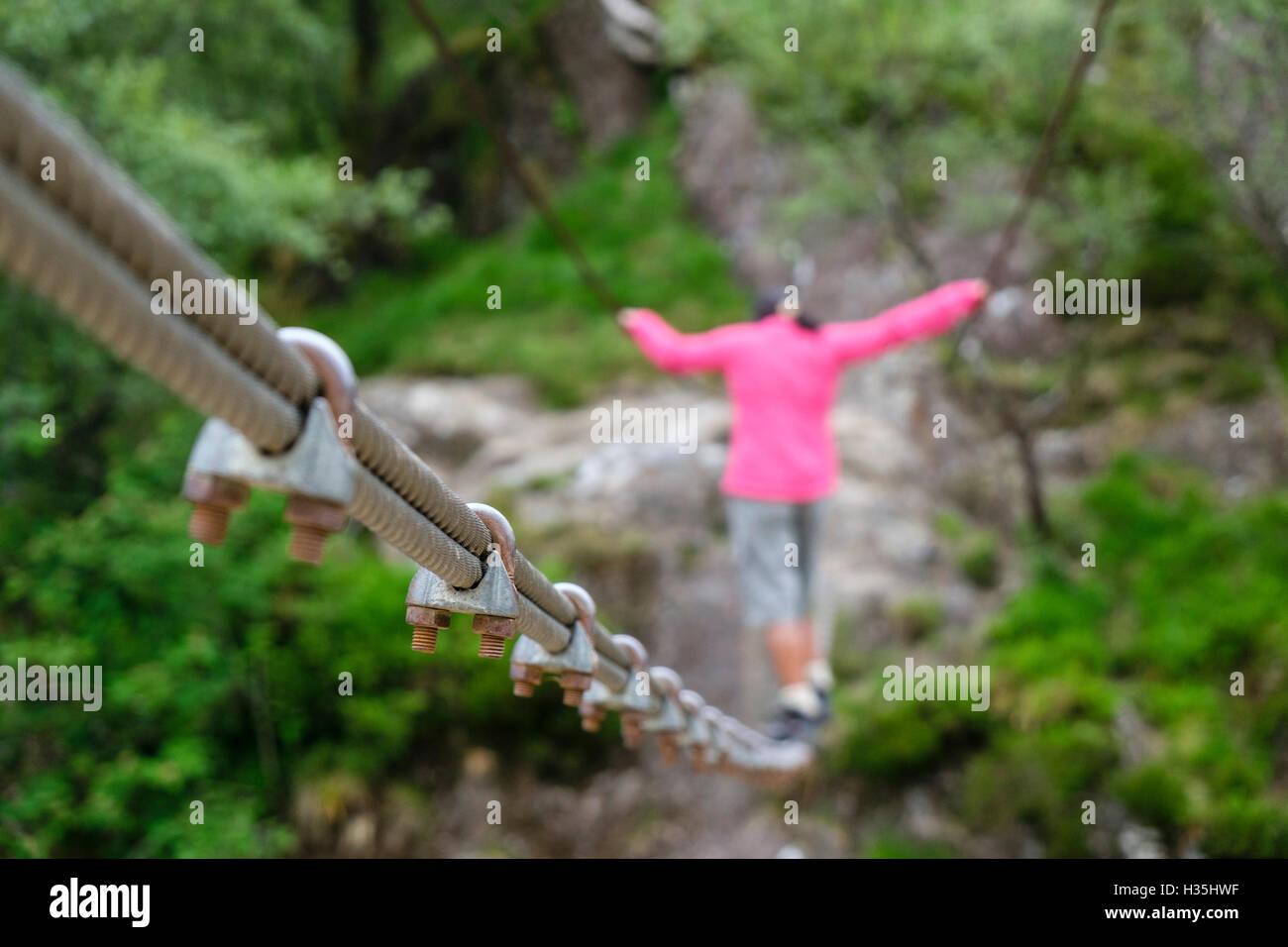 Asiatische Frau zu Fuß über Steall Drahtseil Brücke über Fluss Nevis ...