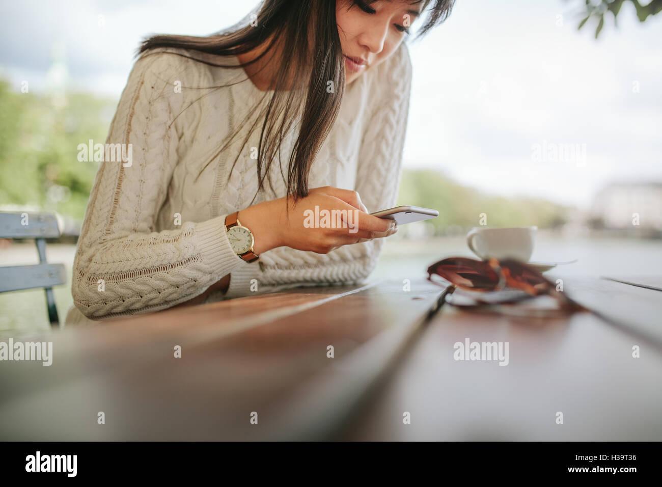Frau Textmitteilung auf smart Phone in einem Café zu schreiben. Foto von junge Frau sitzt an einem Tisch mit Stockbild