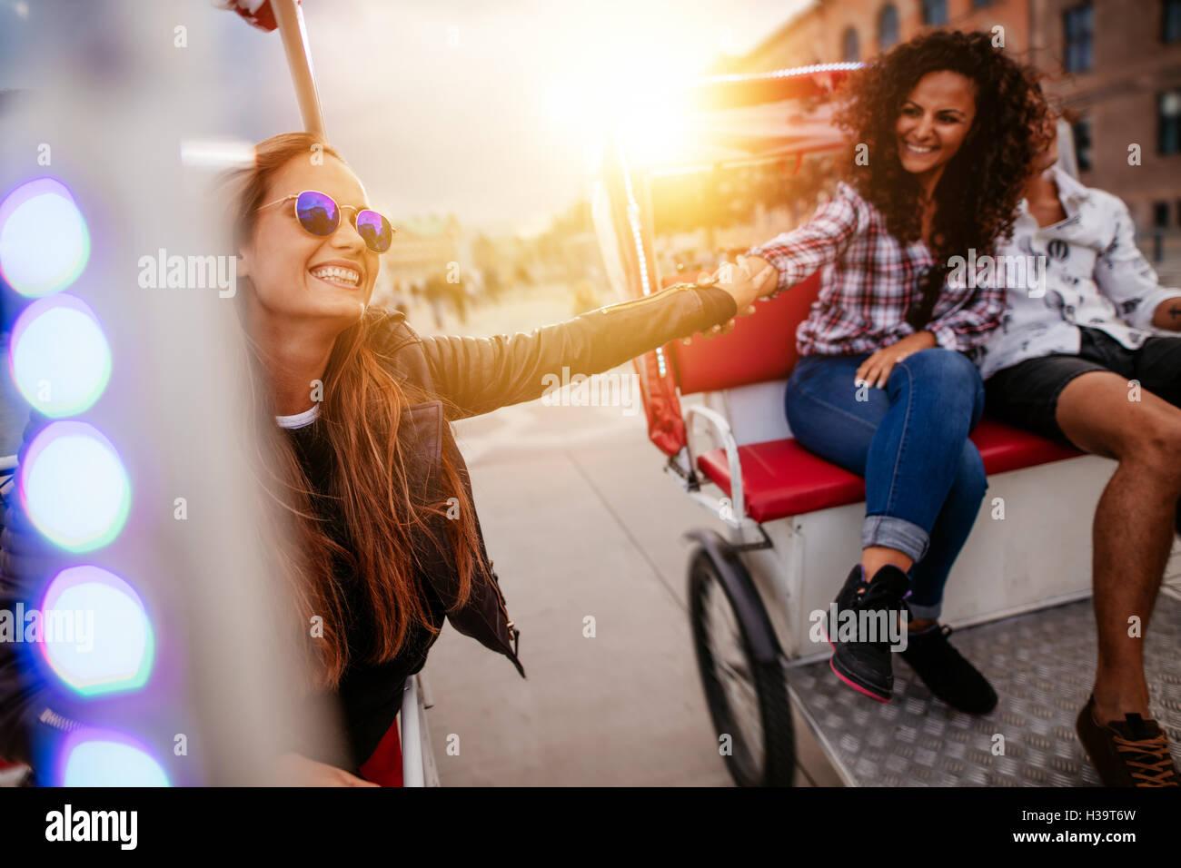 Beste Freunde genießen Dreirad fahren in der Stadt. Teenager-Mädchen reiten auf Dreiräder und Hand Stockbild
