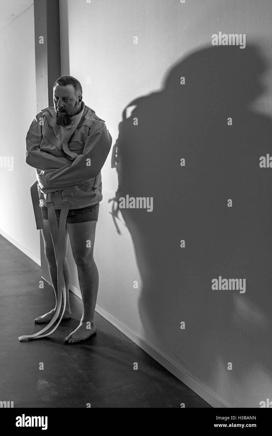 Foto von einem wahnsinnigen Mann in seinen Vierzigern, tragen eine Zwangsjacke stehend in einem Flur einer Asyl. Stockbild
