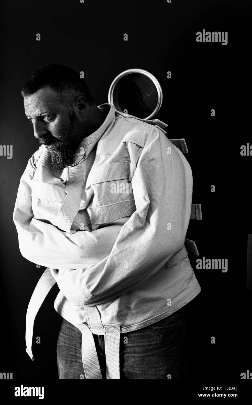 Foto von einem wahnsinnigen Mann in seinen Vierzigern, tragen eine Zwangsjacke, die gegen ein Asyl Tür gelehnt. Stockbild