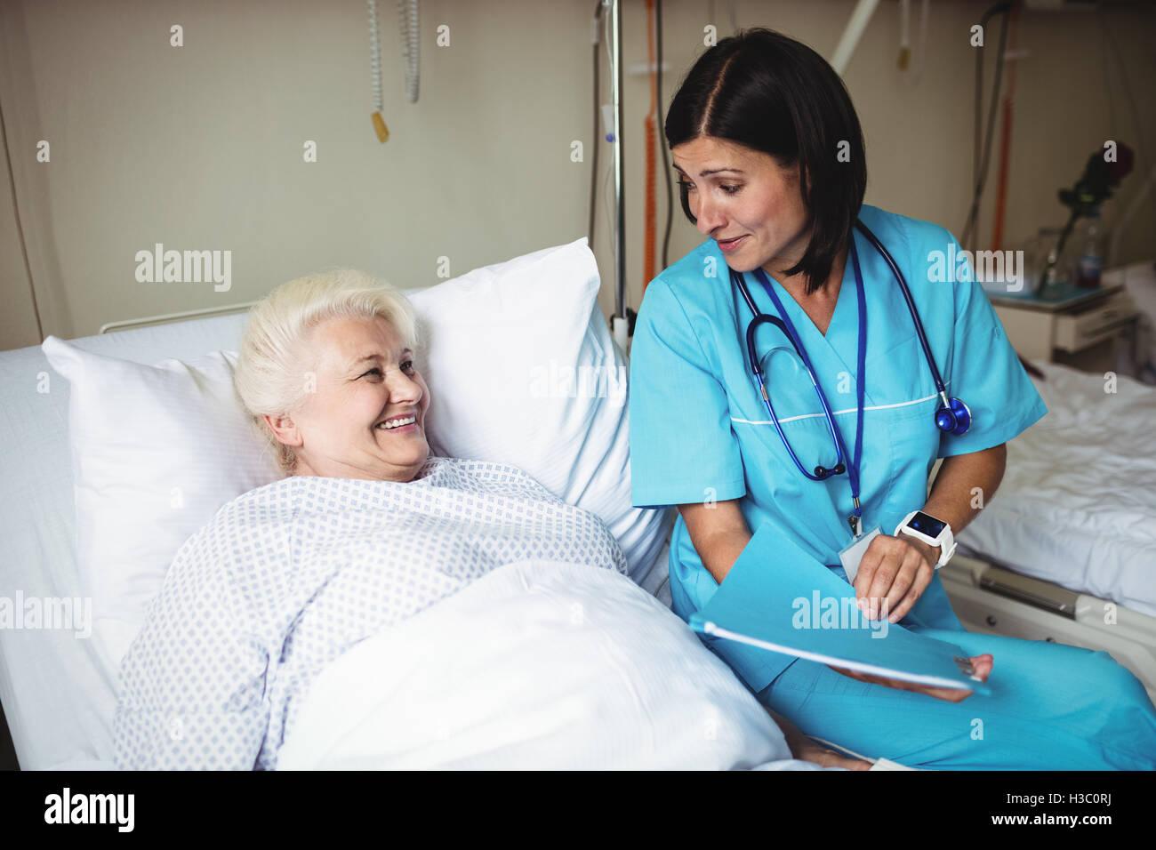 Krankenschwester, die Interaktion mit älteren Patienten Stockbild