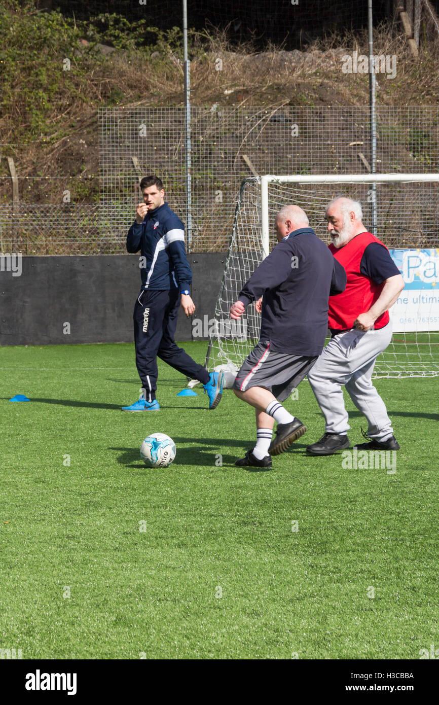 Männer mittleren Alters, die an einem Fuß Fußball teilnehmen in Bolton, organisiert Lancashire, von Stockbild