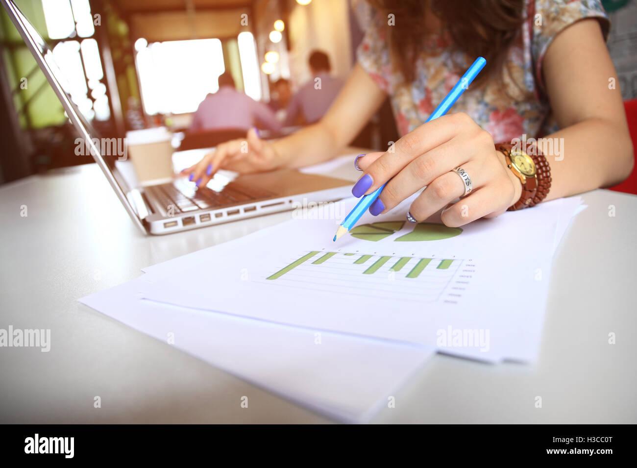 Unternehmensberater, die Analyse von Finanzkennzahlen bezeichnet den Fortschritten bei der Tätigkeit des Unternehmens Stockfoto