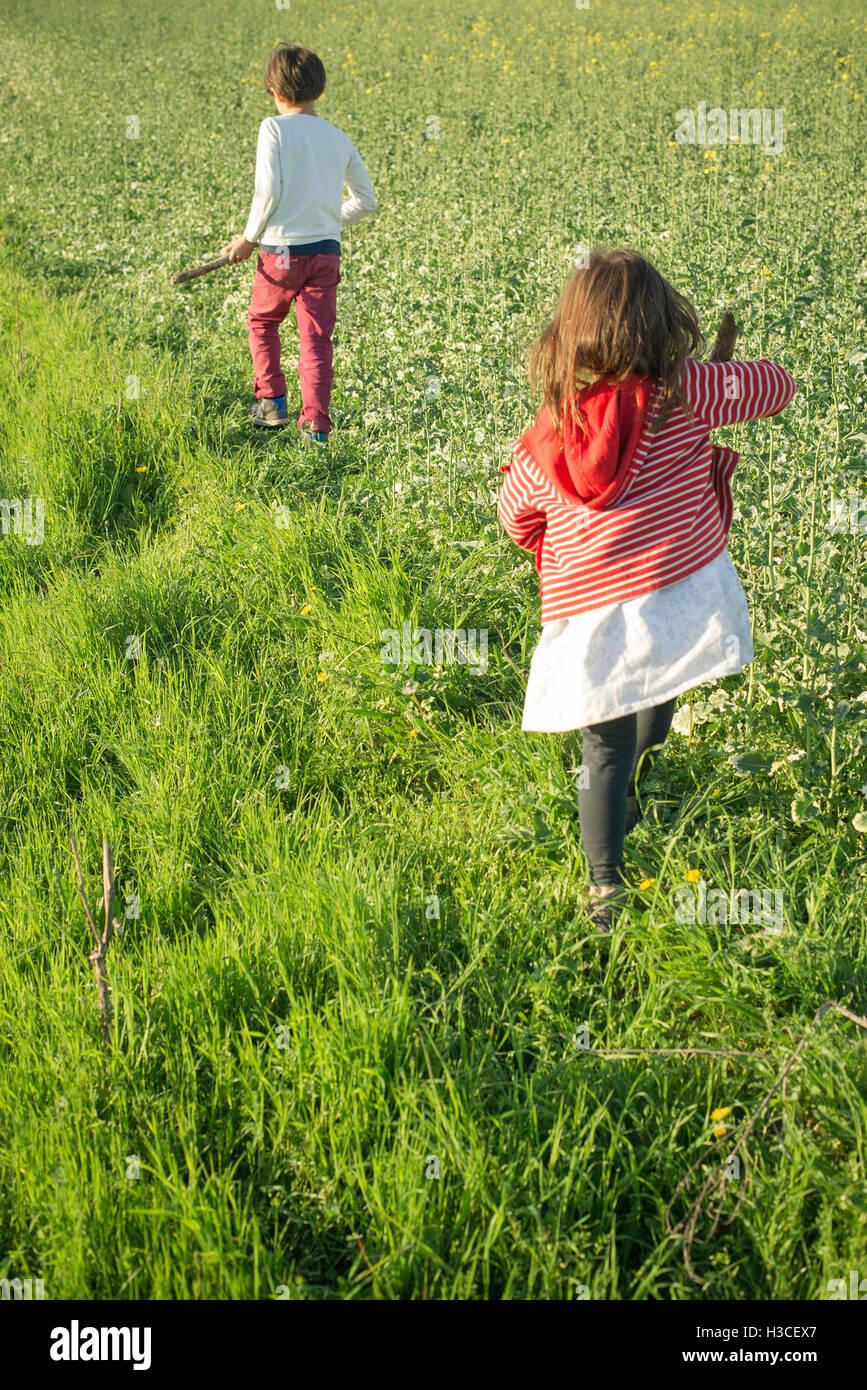 Kinder zu Fuß in Feld, Rückansicht Stockfoto