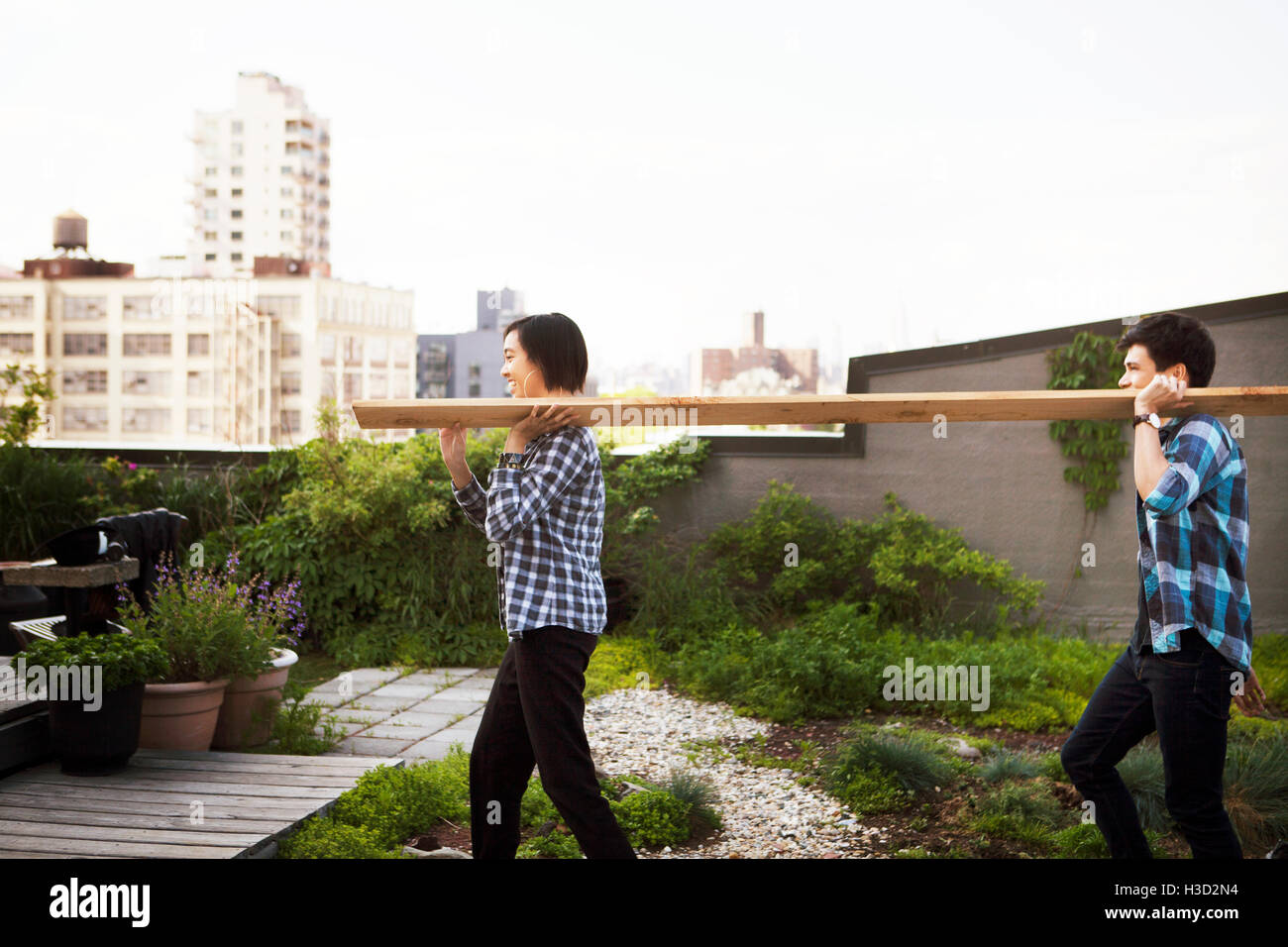 Seitenansicht des Paares tragen Holzbrett während des Gehens auf Terrasse Stockfoto