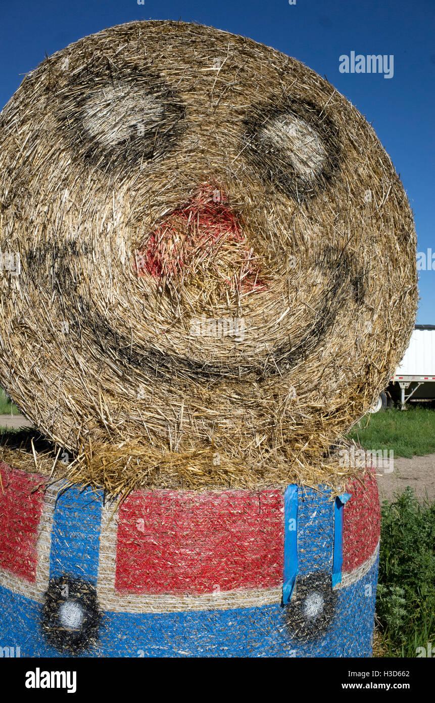 Lächelnde Minion-Cartoon-Figur gemacht vom Bauernhof Rollen Heu tragen blaue Hosen und roten Hemd. Clitherall Stockbild