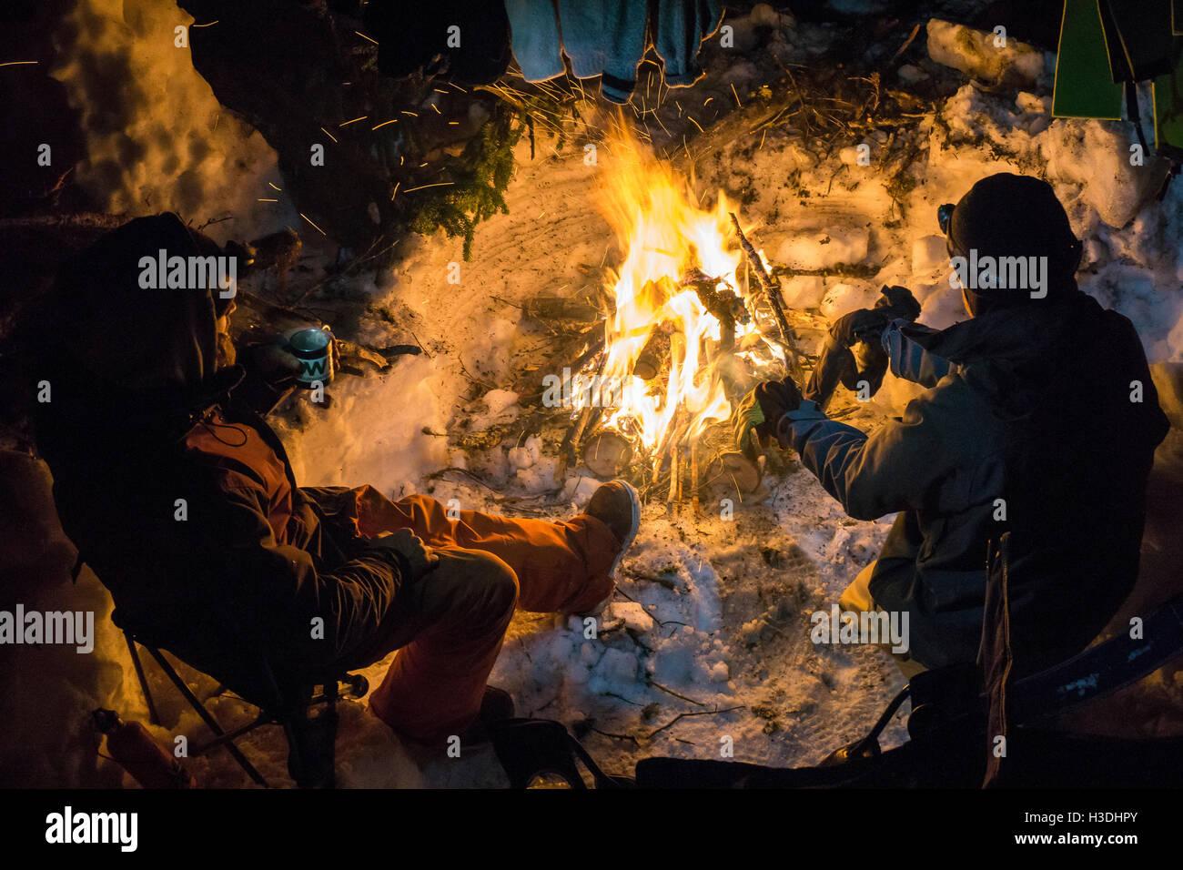 Snowboarden, Teetrinken Lagerfeuer am Abend Aufwärmen Stockbild