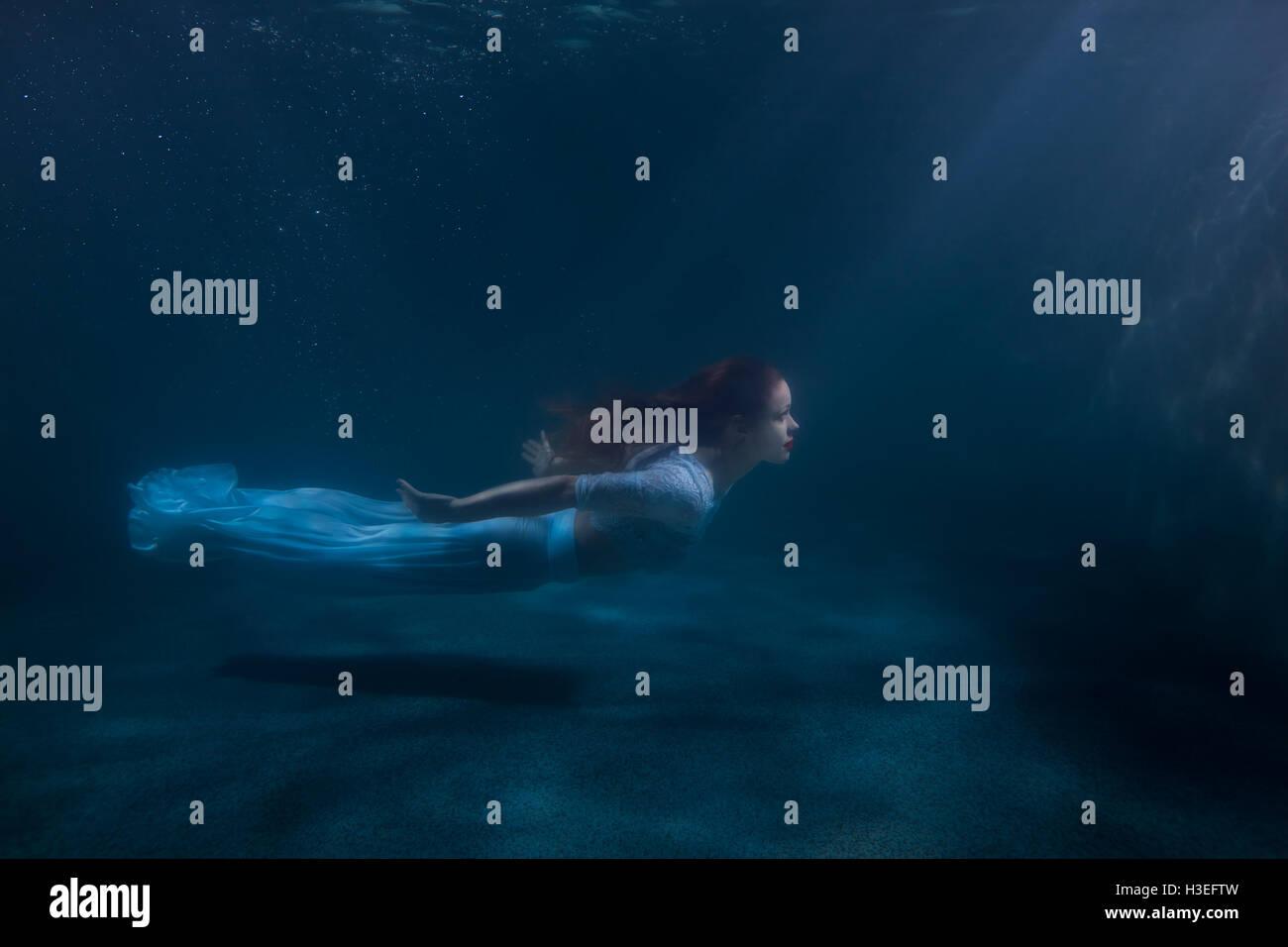 Frau als die Meerjungfrau schwimmt unter Wasser, sie in einem weißen Kleid. Stockbild