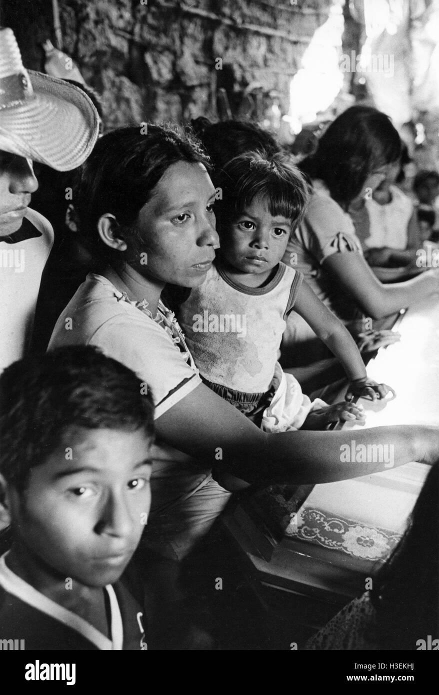 EL TRIUMFO, EL SALVADOR März 1982: Frauen warten mit den Särgen ihrer Ehemänner, Milizangehörigen Stockbild