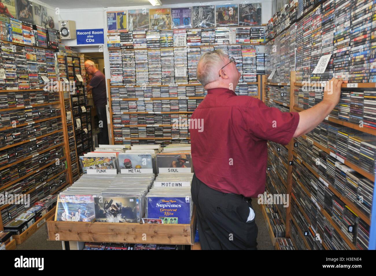 Zwei Männer mittleren Alters durchsuchen die CD- und DVD-Regale in einem Datensatz und DVD shop Stockbild