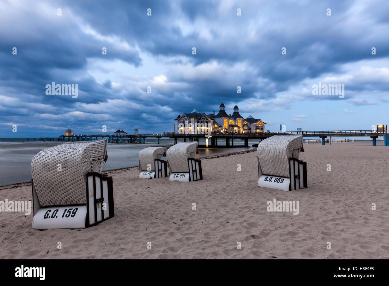 Liegestühle vor dem beleuchteten Pier der Ostsee Ostseebad Sellin, Rügen, in der Dämmerung Stockfoto
