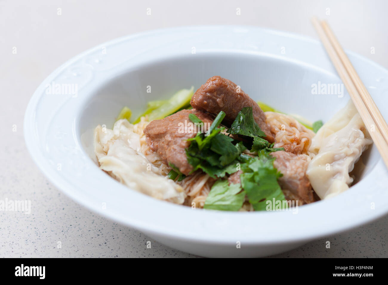 Eiernudeln mit köstlich geschmortes Schweinefleisch und Knödel in weiße Schüssel. Stockbild