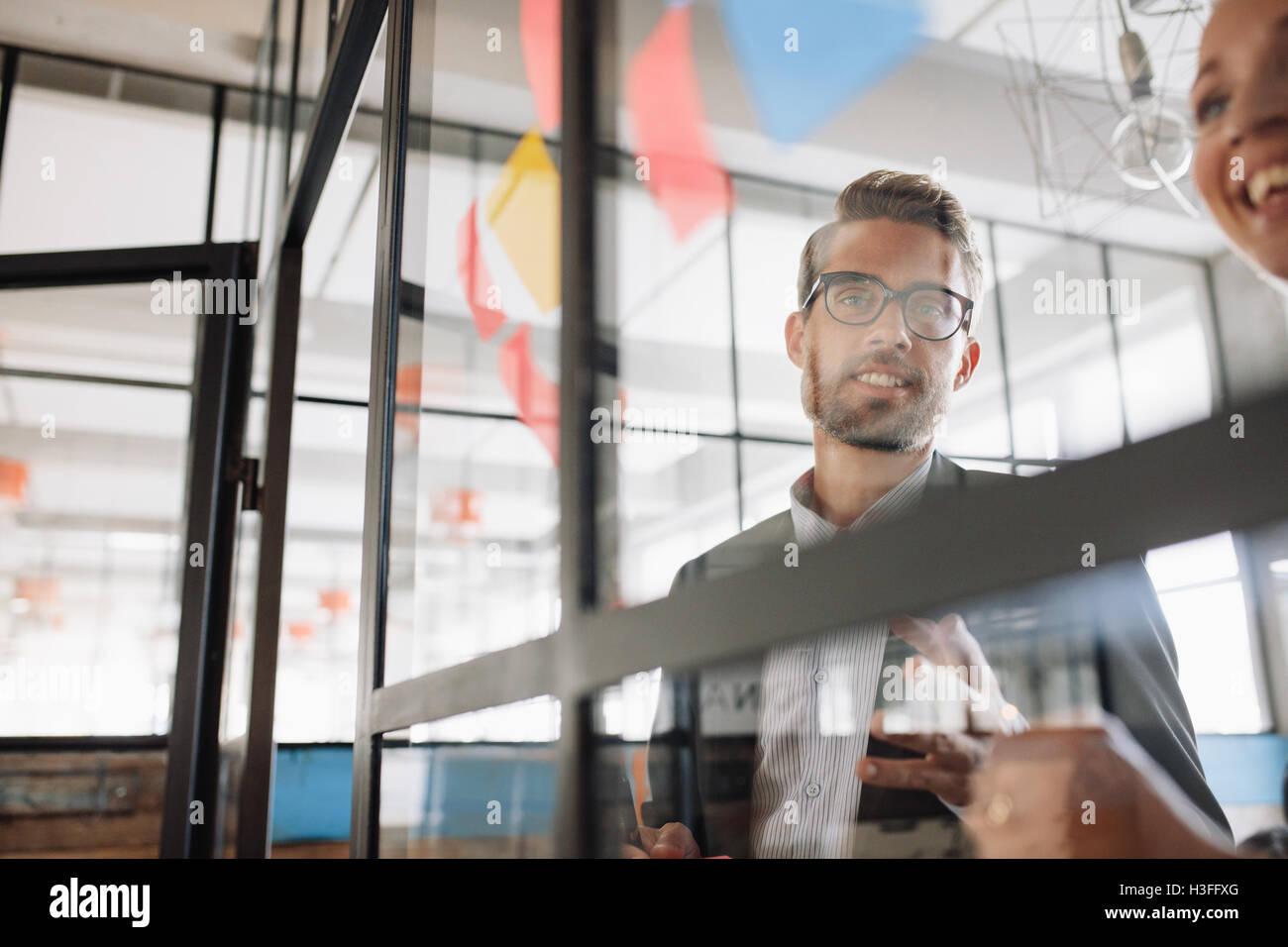 Porträt des jungen Geschäftsmann mit Kollegin betrachten Klebstoff Notizen auf Glaswand und Brainstorming. Stockbild