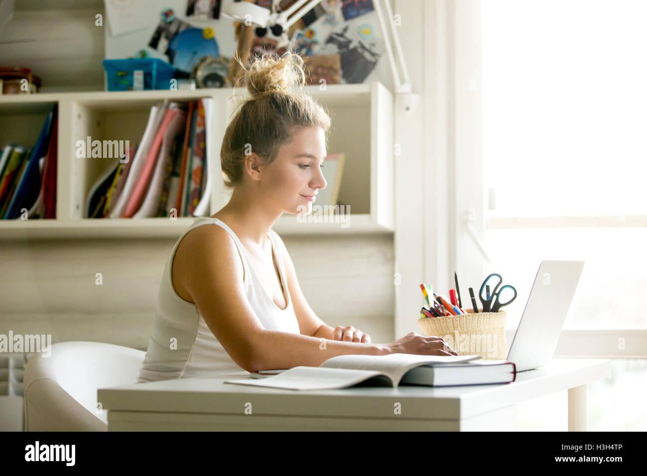 Junge Frau im gemütlichen Heim-Büro Stockbild
