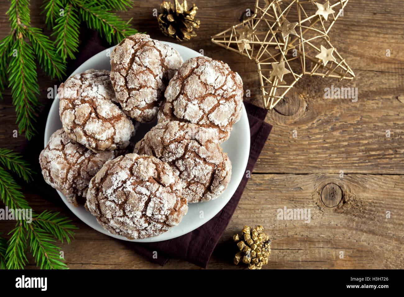Schokolade crinkle Cookies für Weihnachten mit goldenen Ormaments und Tanne Äste - festliche hausgemachte Stockbild