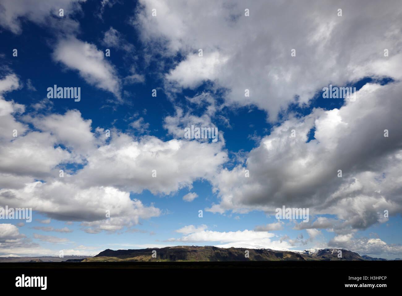 weiße Wolken am blauen Himmel über offene Nutzflächen im Süden Islands Stockbild