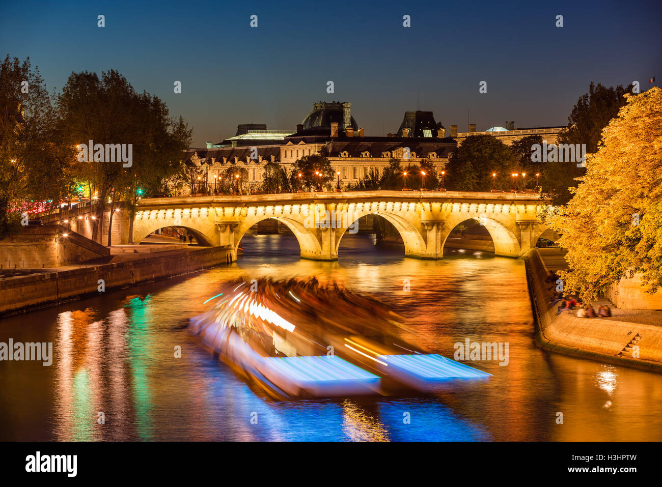 Pont Neuf Brücke beleuchtet und Seineufer in der Dämmerung mit Citylights und Touristenboot. Ile De La Stockbild