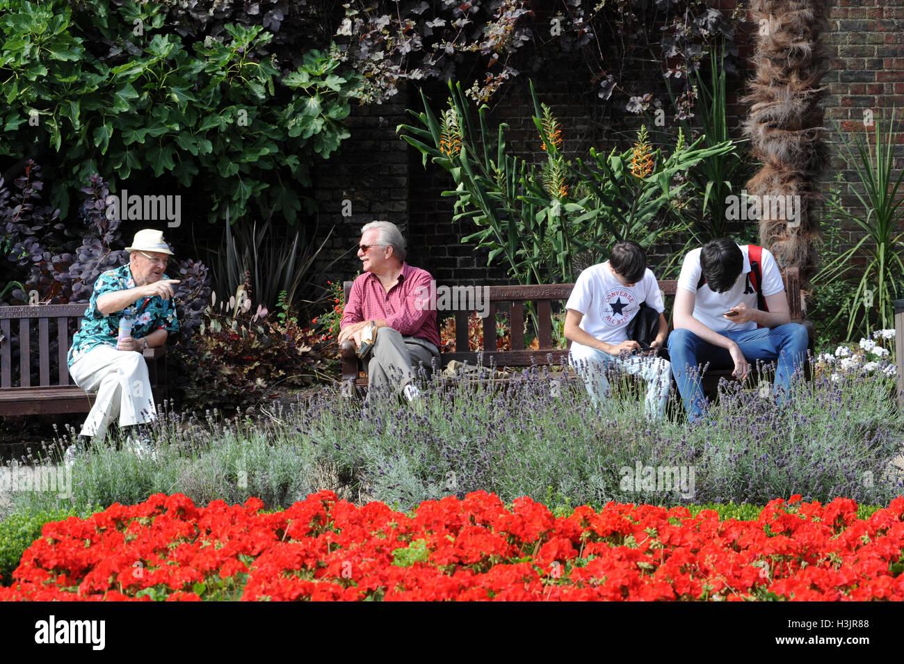 Zwei ältere Herren sitzen auf einer Parkbank im Chat, während zwei Kinder neben ihnen Pokemon spielen. Stockfoto