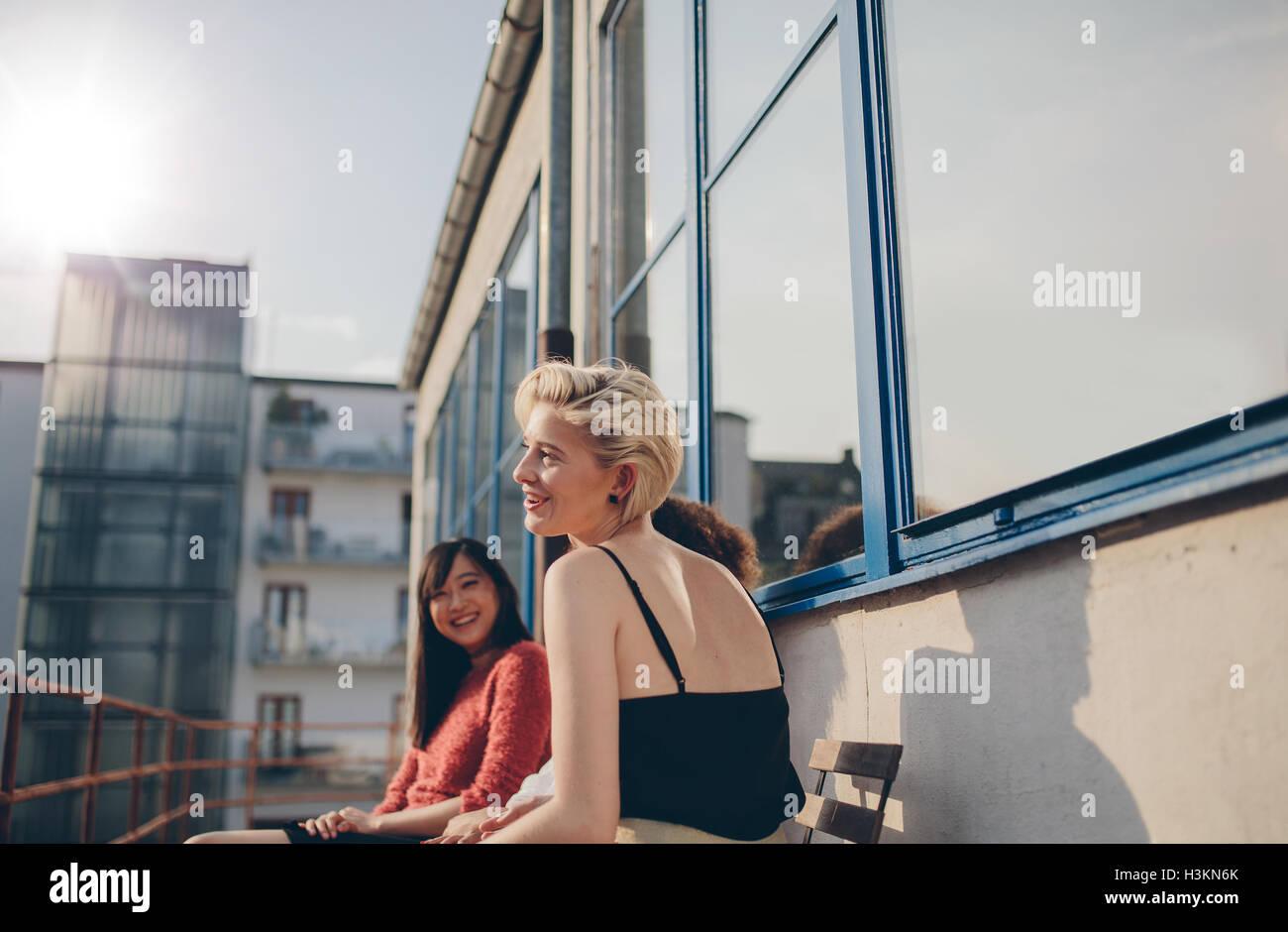 Drei junge Frauen sitzen auf Balkon an einem sonnigen Tag. Freundinnen genießen freie Zeit zusammen im Freien. Stockbild
