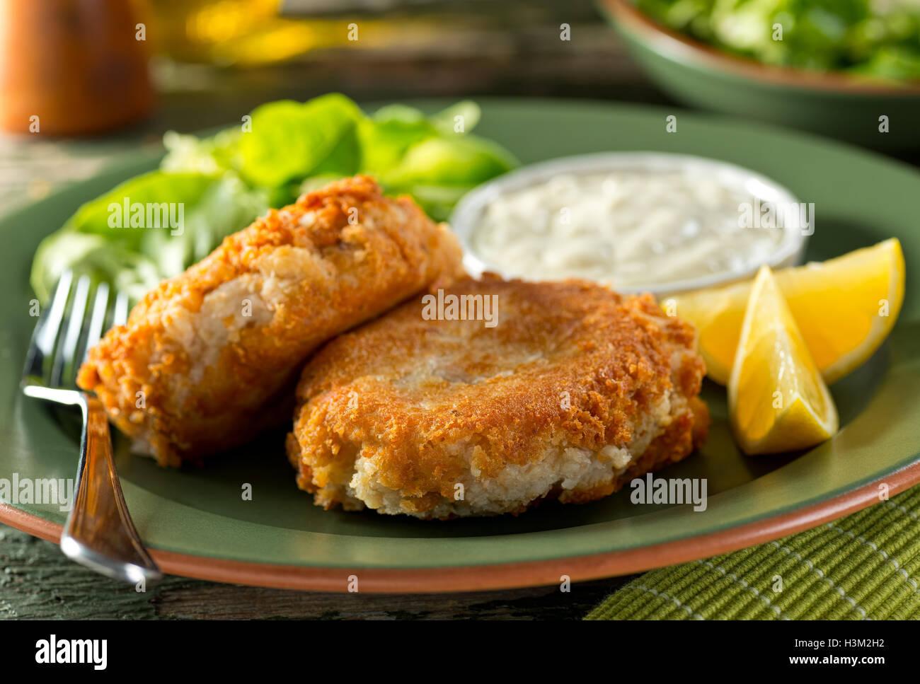 Ein Teller mit leckeren selbstgemachten Fischfrikadellen mit Zitronen, grüner Salat und Remoulade. Stockbild
