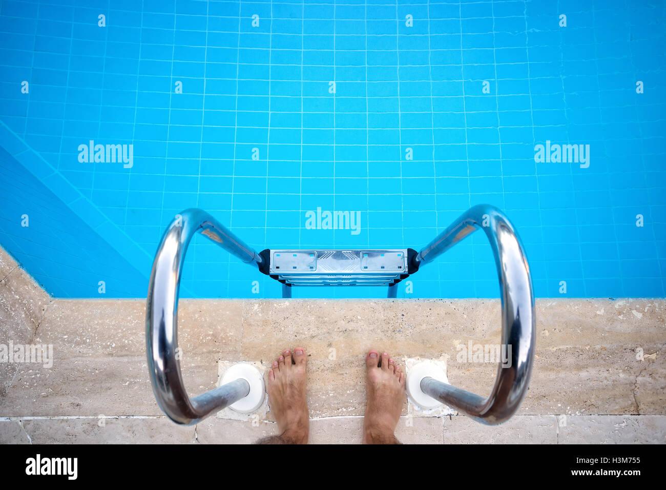 Füße in der Nähe von der Treppe in den Pool von oben geschossen Stockbild