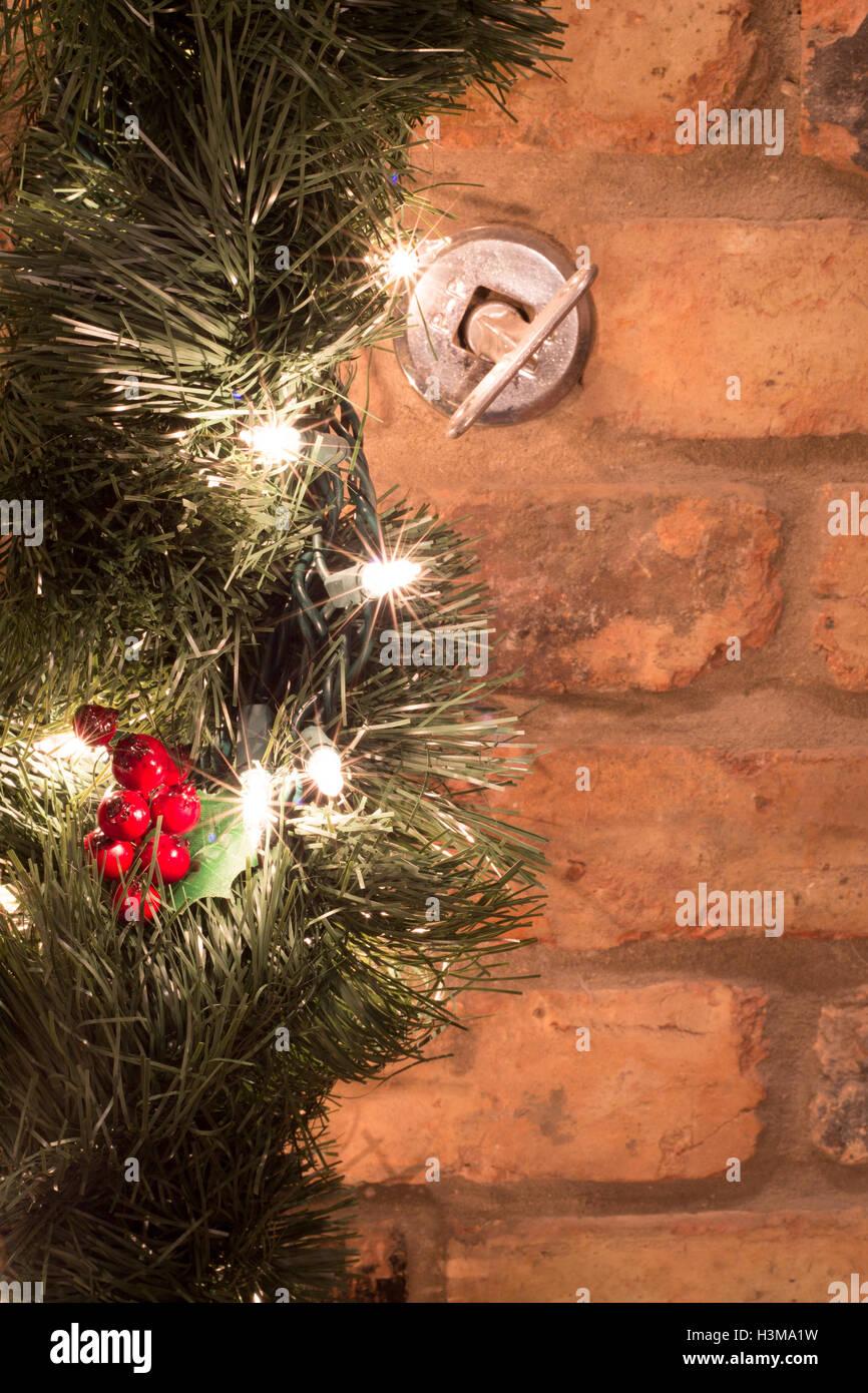 Grüne Weihnachten Kranz Mit Roten Stechpalme Beeren Und Weißen  Weihnachtsbeleuchtung Von Backstein Kamin Kaminsimses Hängen.