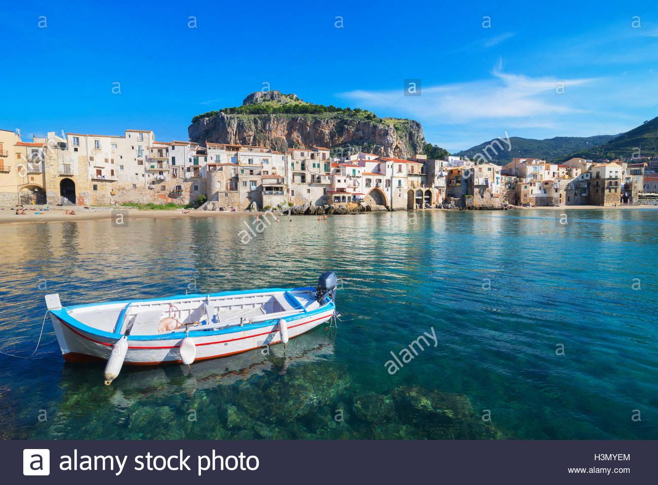 Fischerboot in der Nähe von alte Stadt am Wasser und La Rocca, Cefalu, Sizilien, Italien Stockbild