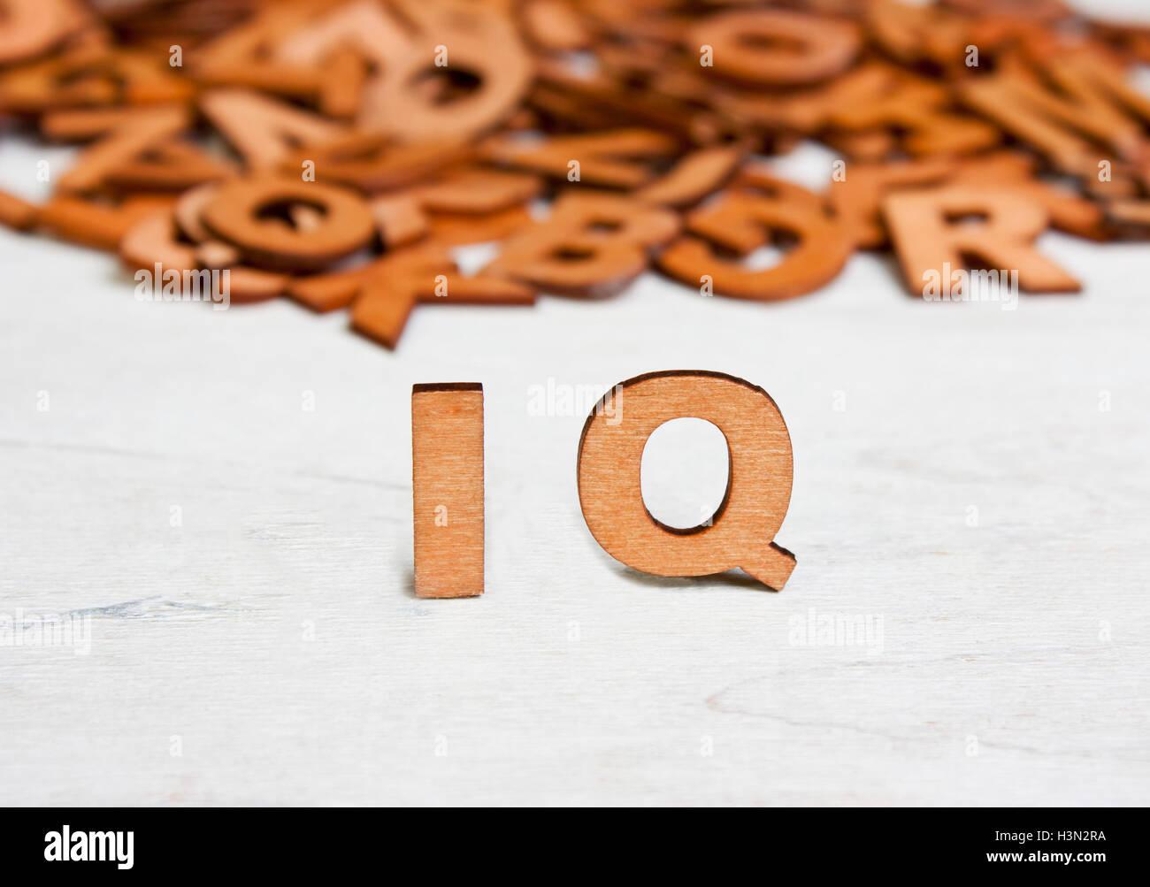 Wort-IQ (Intelligenzquotient) mit Holzbuchstaben auf einem Hintergrund von anderen verschwommenen Buchstaben gemacht Stockbild