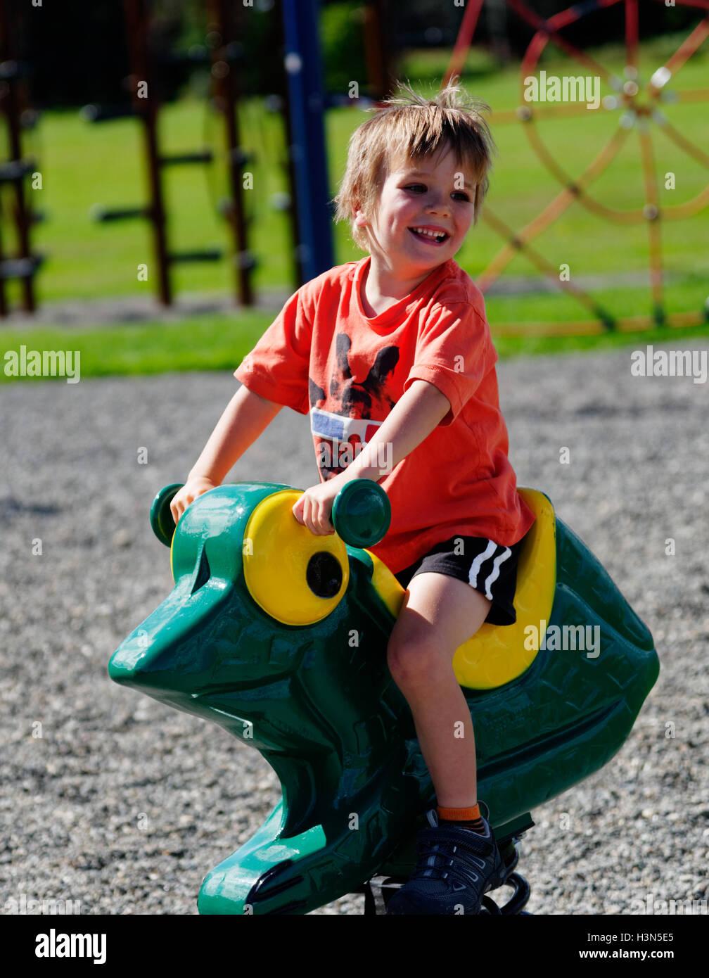 Ein lachendes Kind (4 Jahre alt) hüpfen auf einem Spielplatz Spielzeug Stockbild