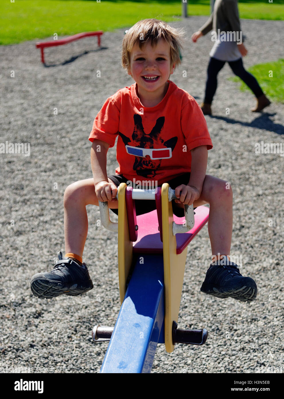 Ein lachendes Kind (4 Jahre alt) Prellen auf einer Wippe Stockbild