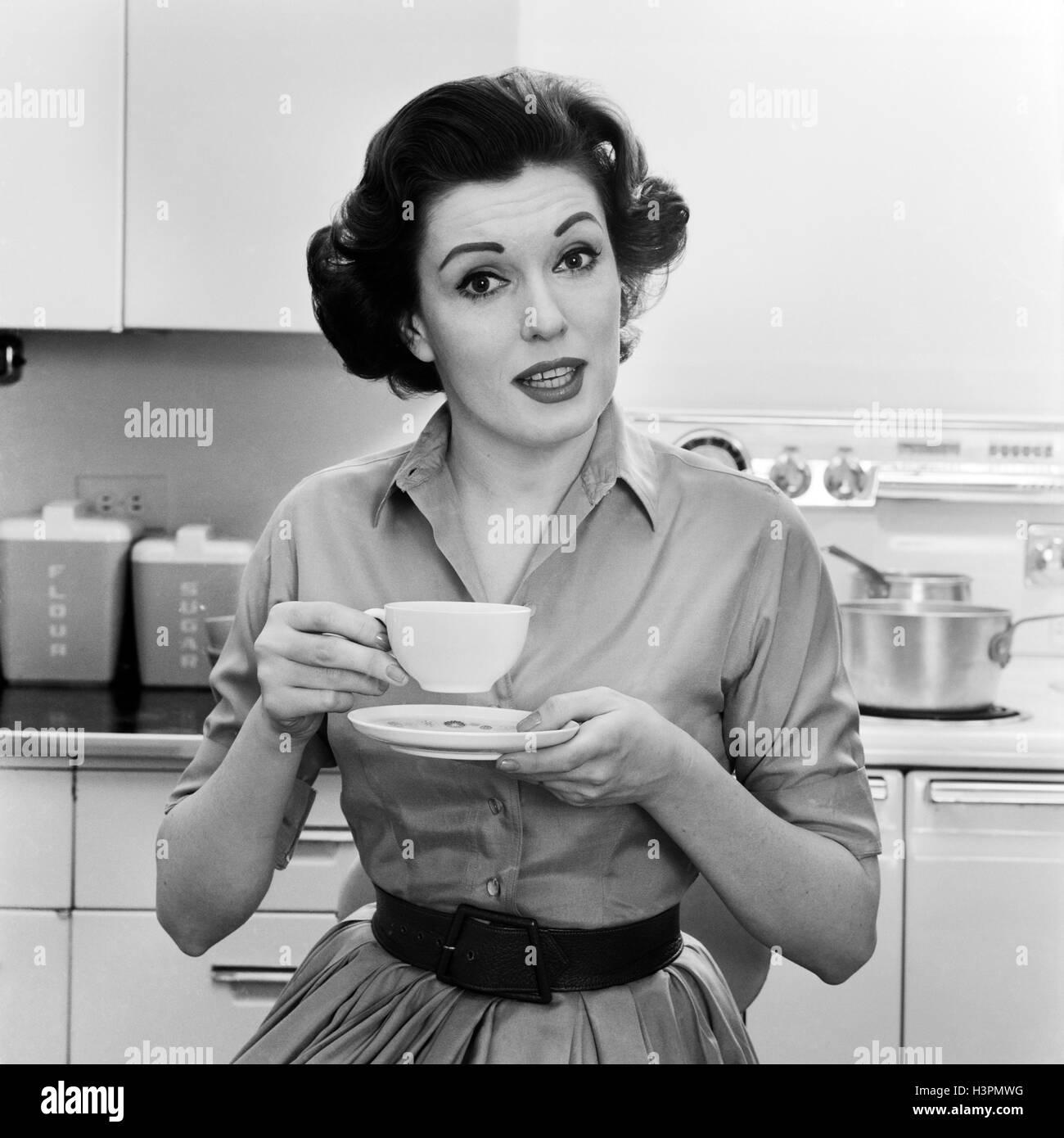 1950S 1960S PORTRAIT FRAU HAUSFRAU IN KÜCHE TRINKEN TASSE KAFFEE SPRECHEN, BLICK IN DIE KAMERA Stockbild